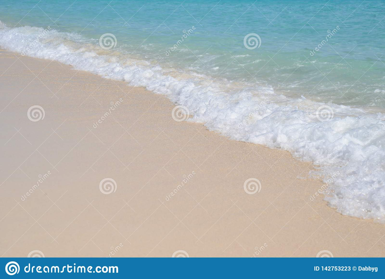 Tropiskt paradis, små vågor som bryter på en kristallklar strand