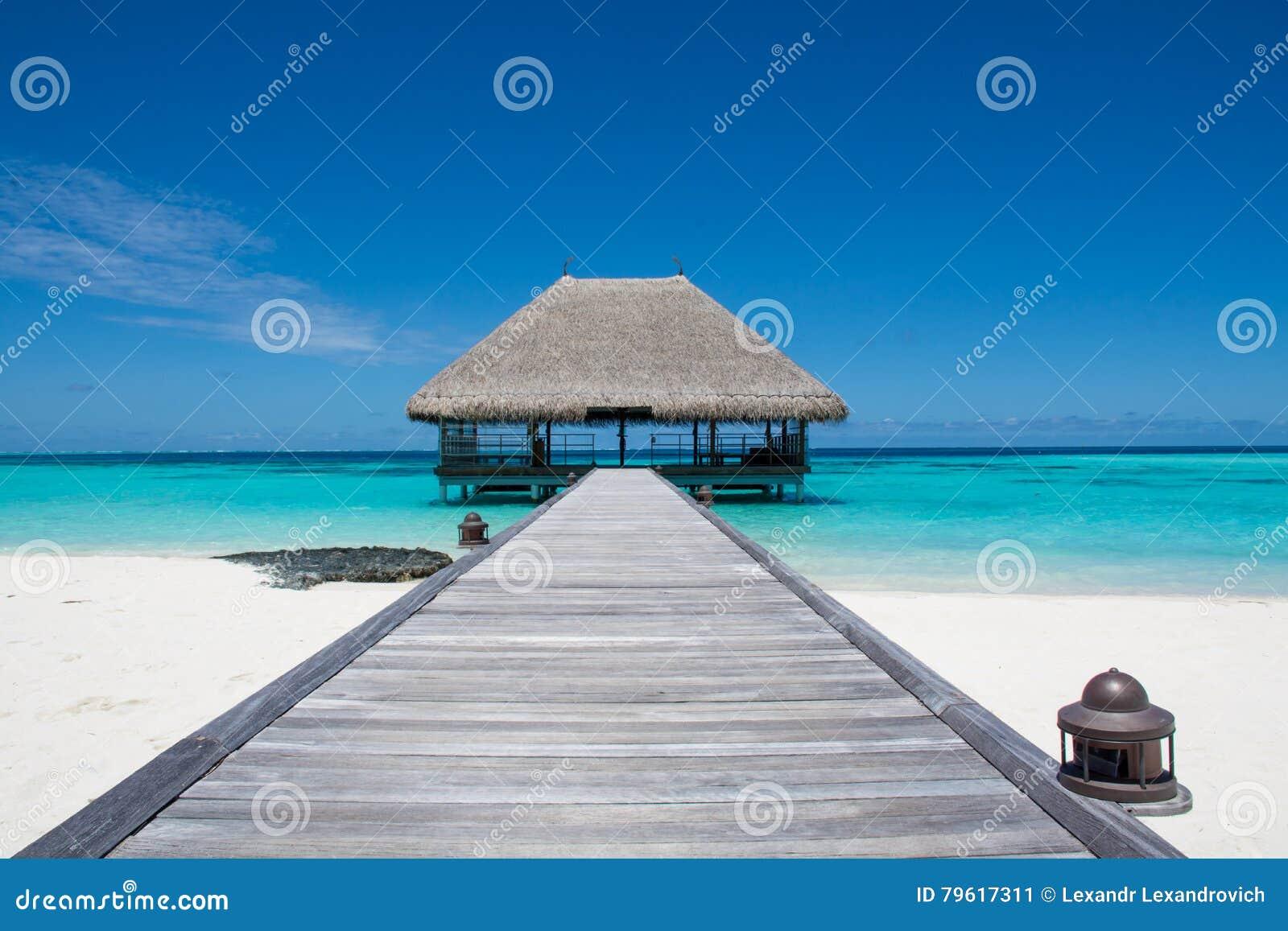 Tropiskt strandlandskap med träbron och huset på vattnet på Maldive