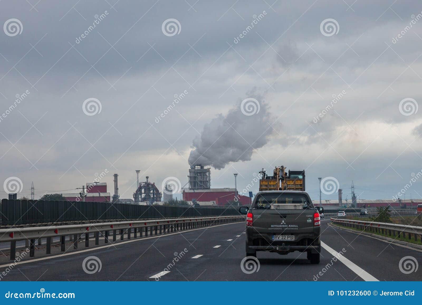 Troquez l entraînement sur une autoroute roumaine près de la route de Sebes, une usine de traitement de bois fortement de polluti