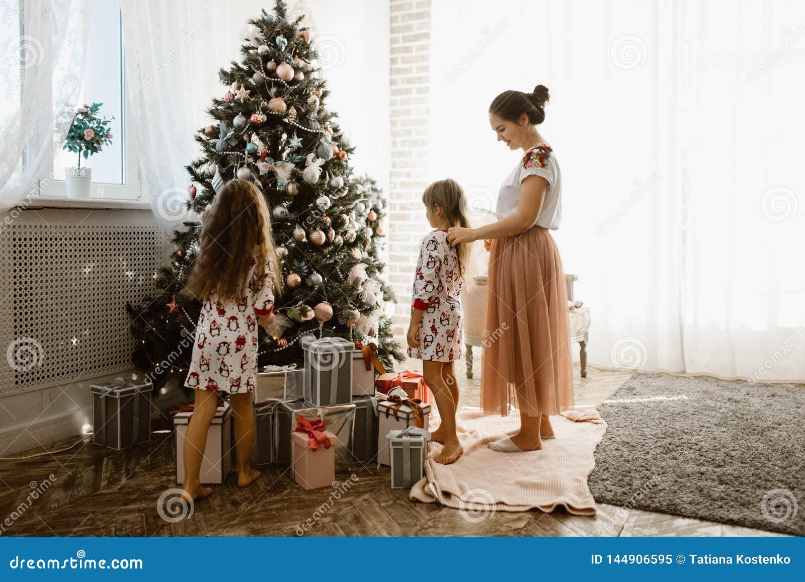 Troskliwa matka splata jej córki małego warkocz podczas gdy drugi córka dekoruje nowego roku drzewa w świetle wygodnym