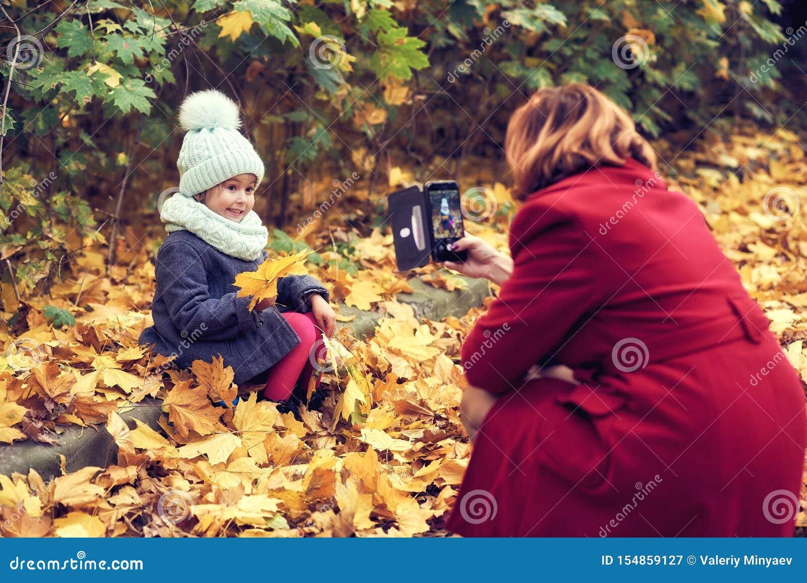 Troszkę dziewczyna pozuje dla jej matki w jesień parku Bierze obrazki z tw?j smartphone