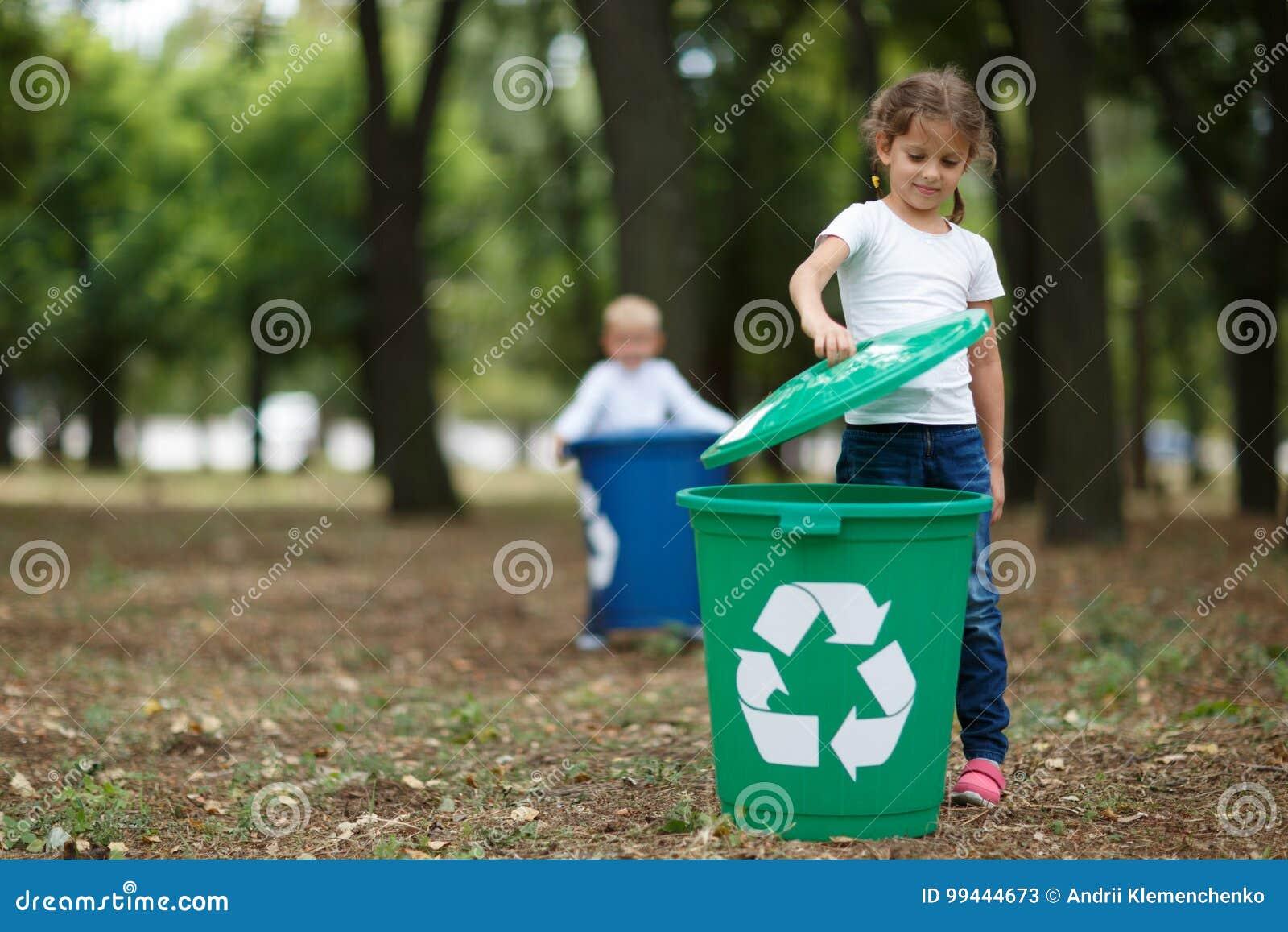 Troszkę dziewczyna stawia wiadro dekiel na zielonym przetwarza koszu na zamazanym naturalnym tle Ekologia i dzieci
