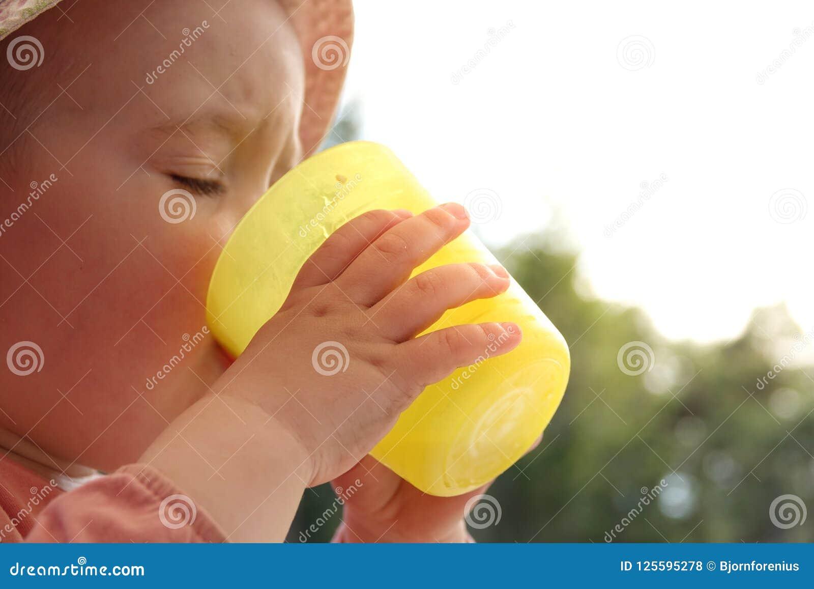 Troszkę dziewczynka napojów woda od plastikowego szkła