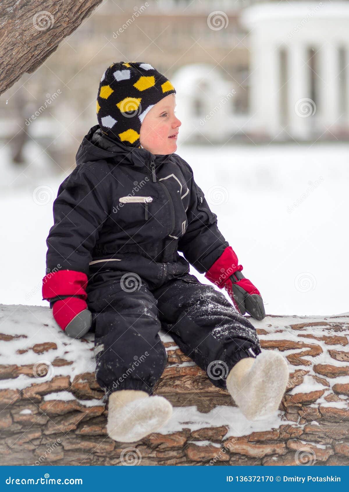 Troszkę siedzi na wielkim spadać drzewie w zimie chłopiec w butach