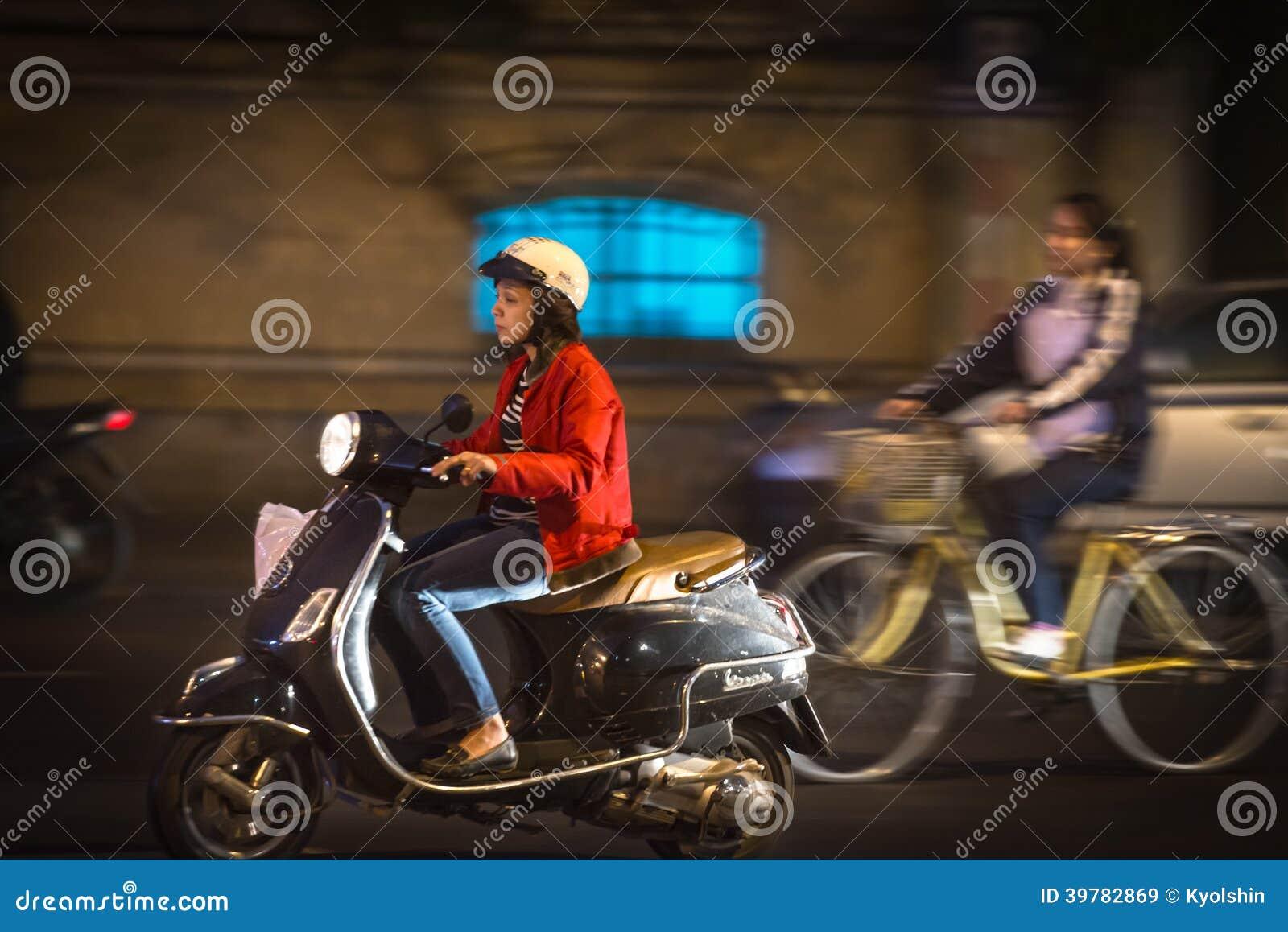 trotinette  da equitação da mulher na noite em Vietname, Ásia.