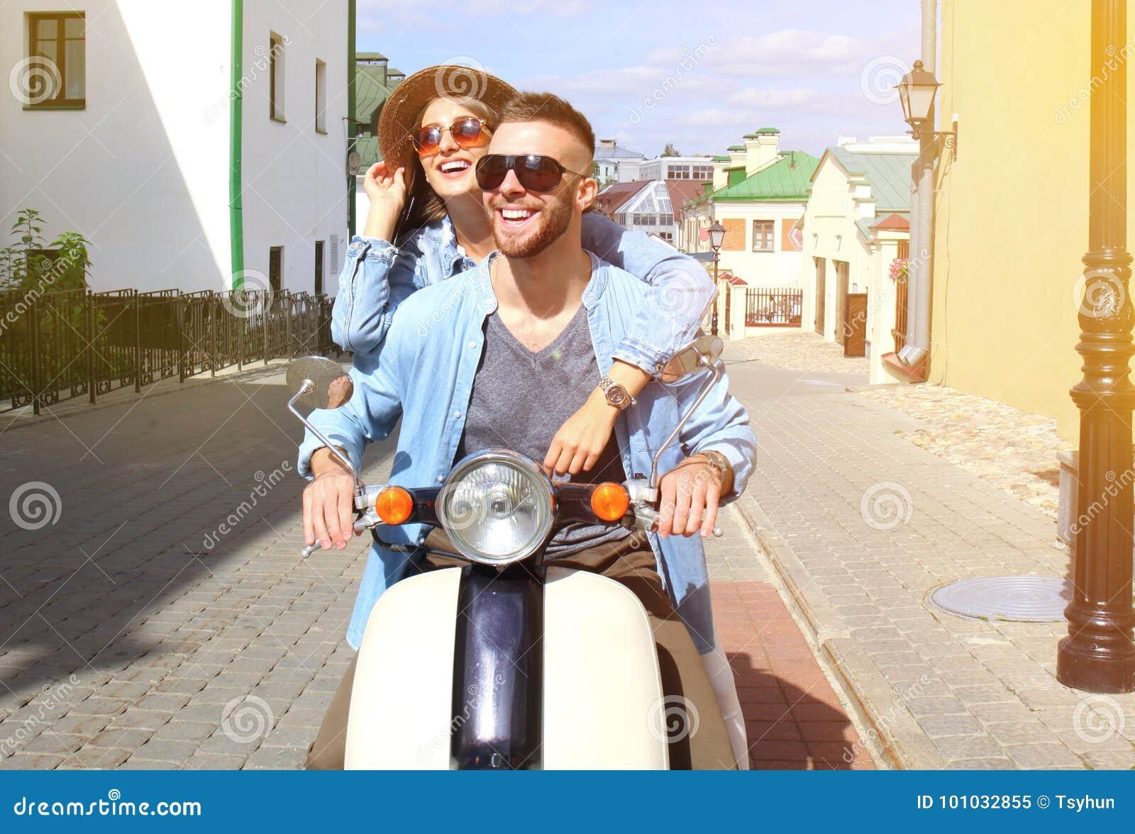 trotinette  novo feliz da equitação dos pares na cidade Curso considerável do indivíduo e da jovem mulher Conceito da aventura e