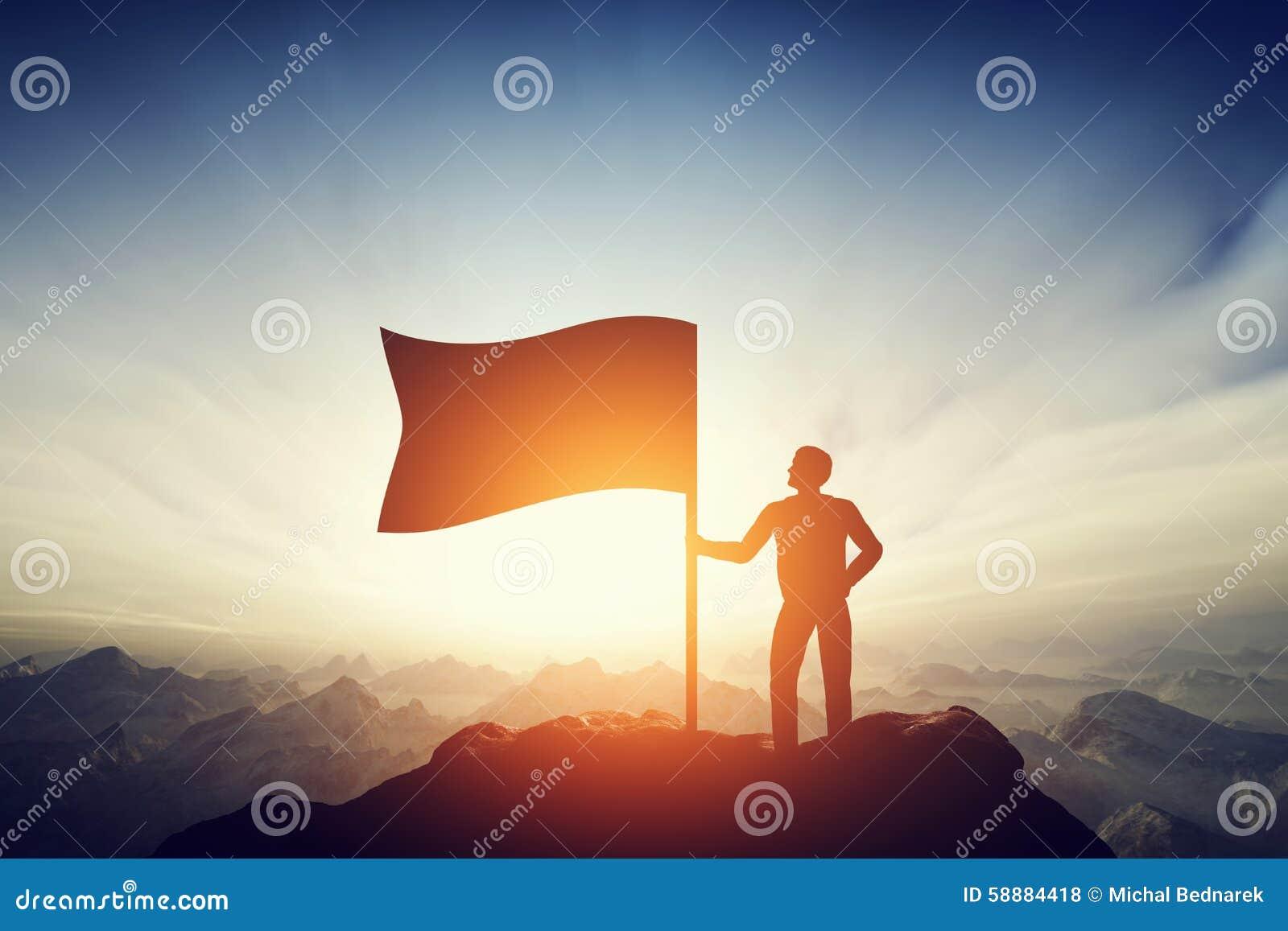 Trotse mens die een vlag op de piek van de berg opheffen Uitdaging, voltooiing