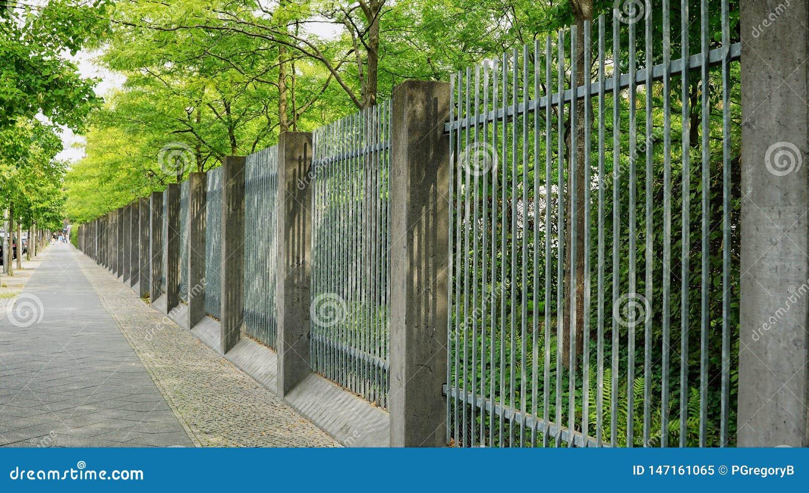 Trottoir bordé d arbres avec la barrière admirablement géométrique