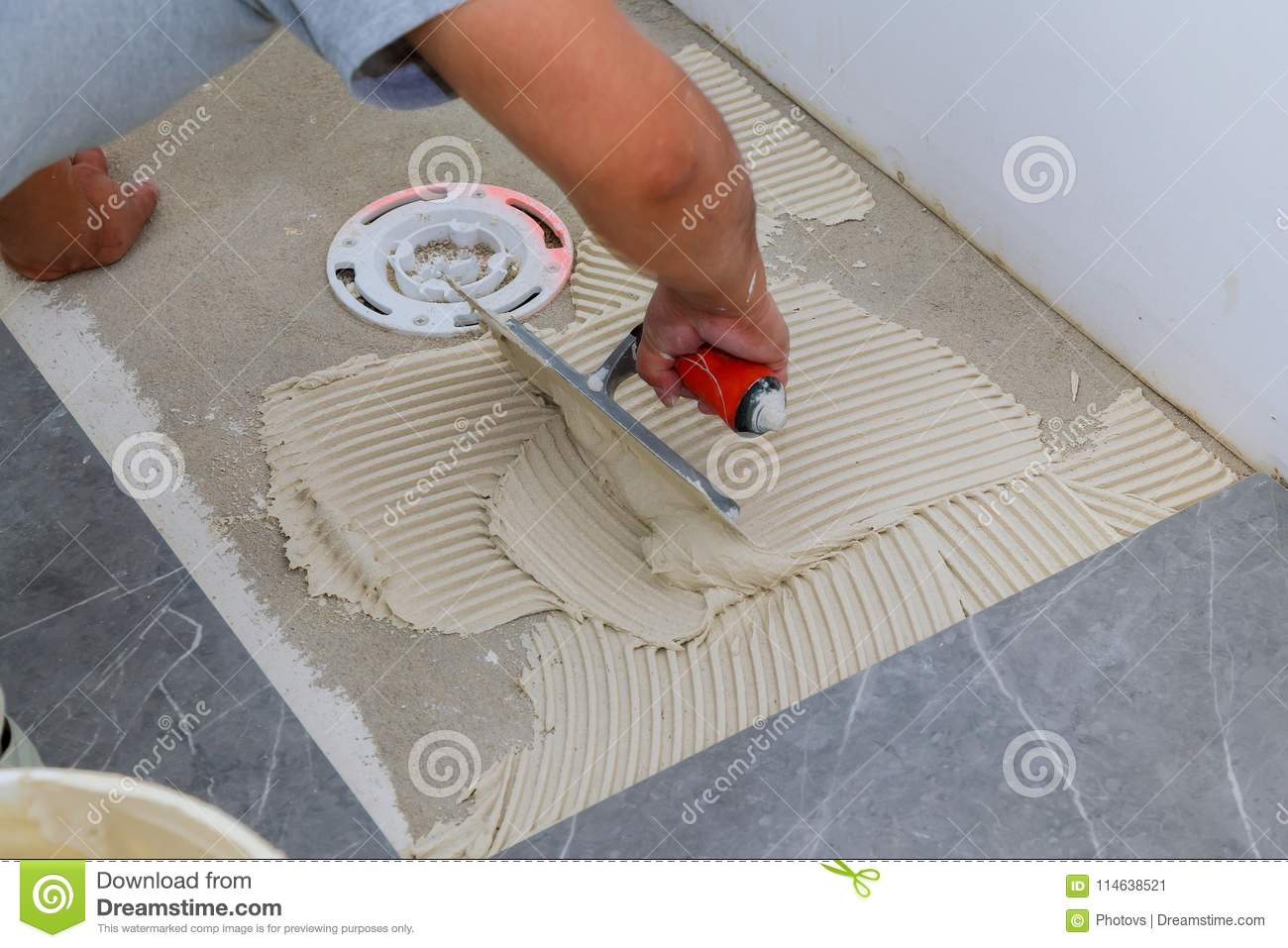 Troweling Mortar Onto A Concrete Floor In Preparation For Floor Tile