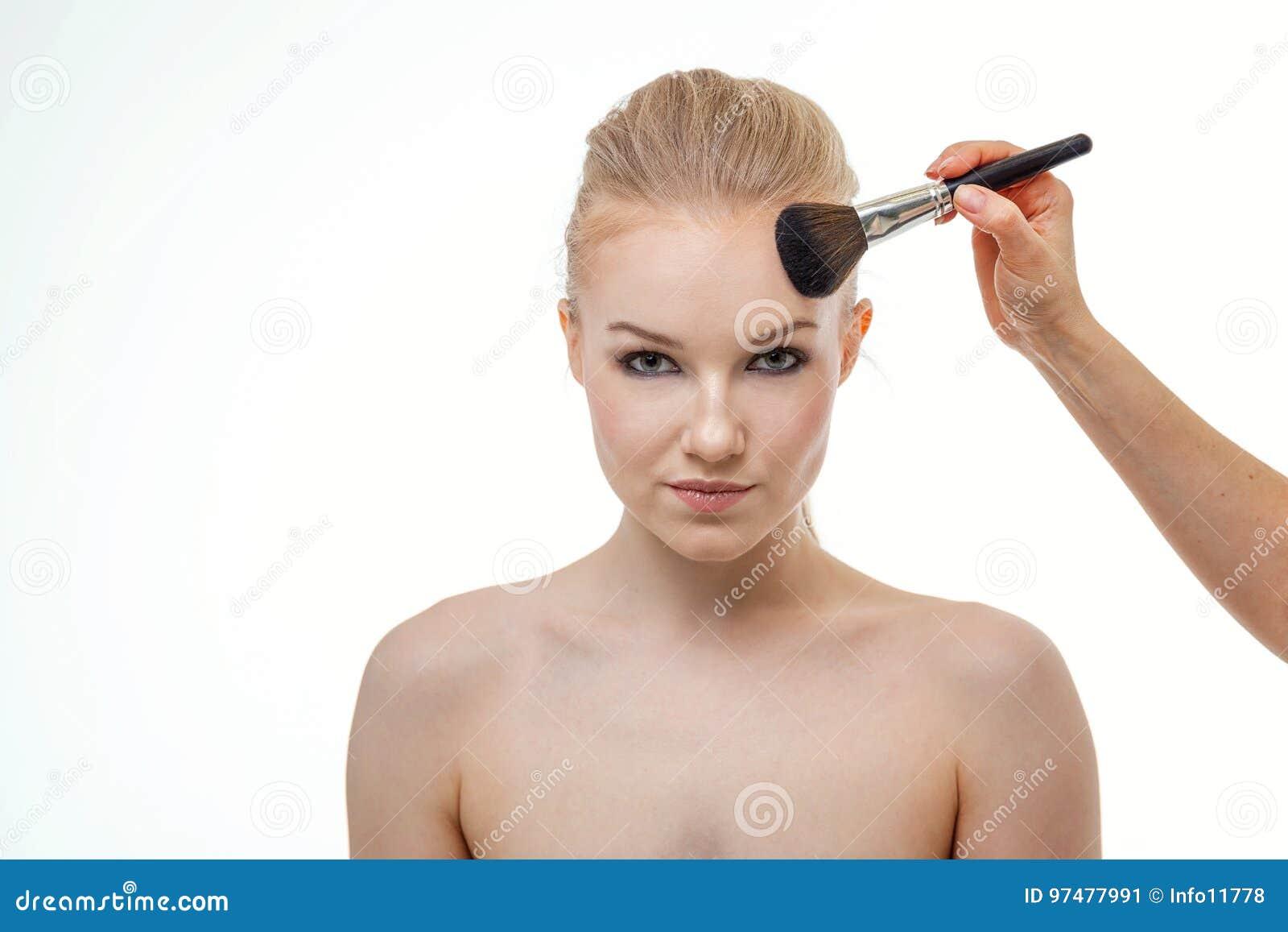Truccatore che applica polvere per la bella giovane donna su fondo bianco