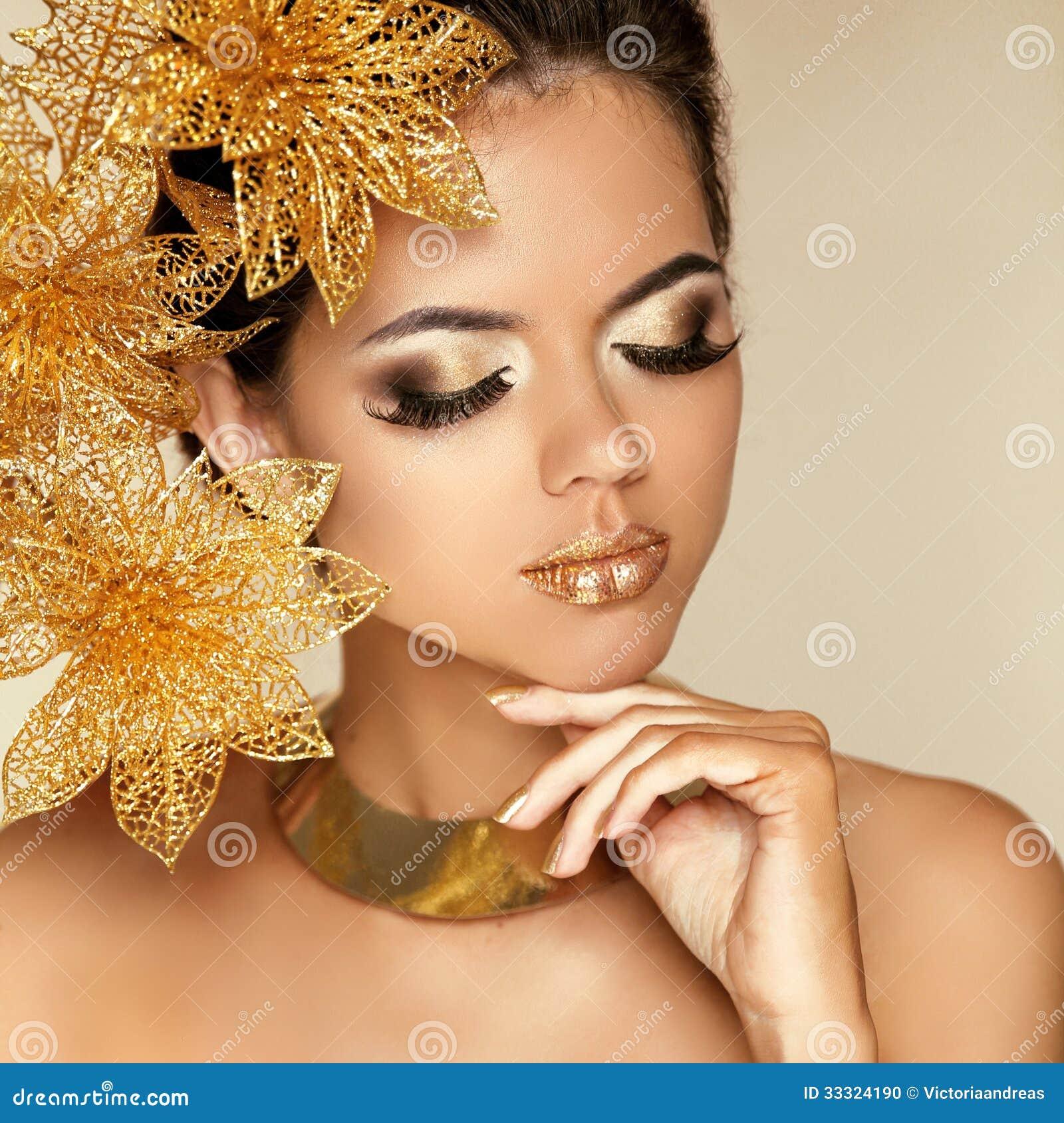 Trucco dell occhio. Bella ragazza con i fiori dorati. Bellezza Wom di modello