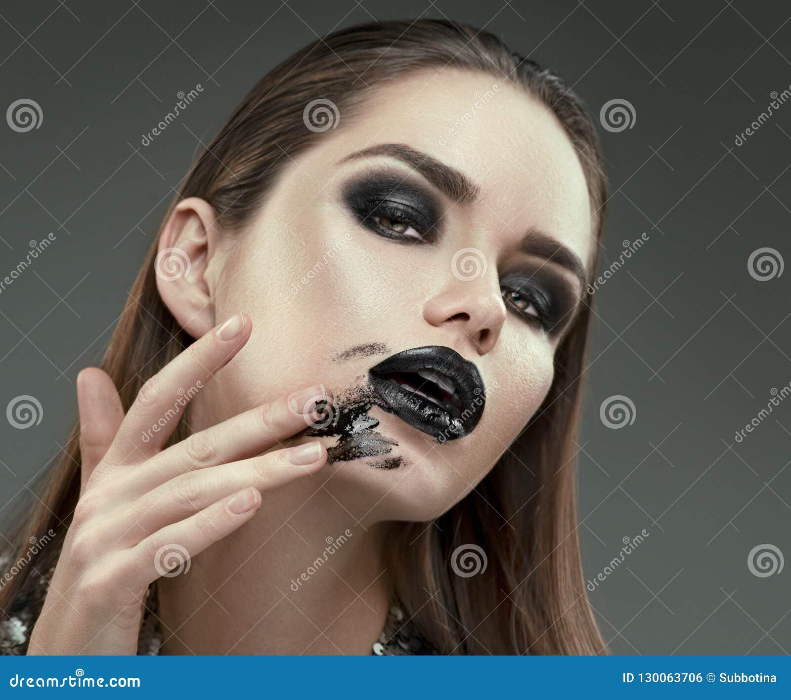 Trucco di Halloween Ragazza del modello di moda con trucco nero gotico d avanguardia La giovane donna spalma il rossetto nero sul