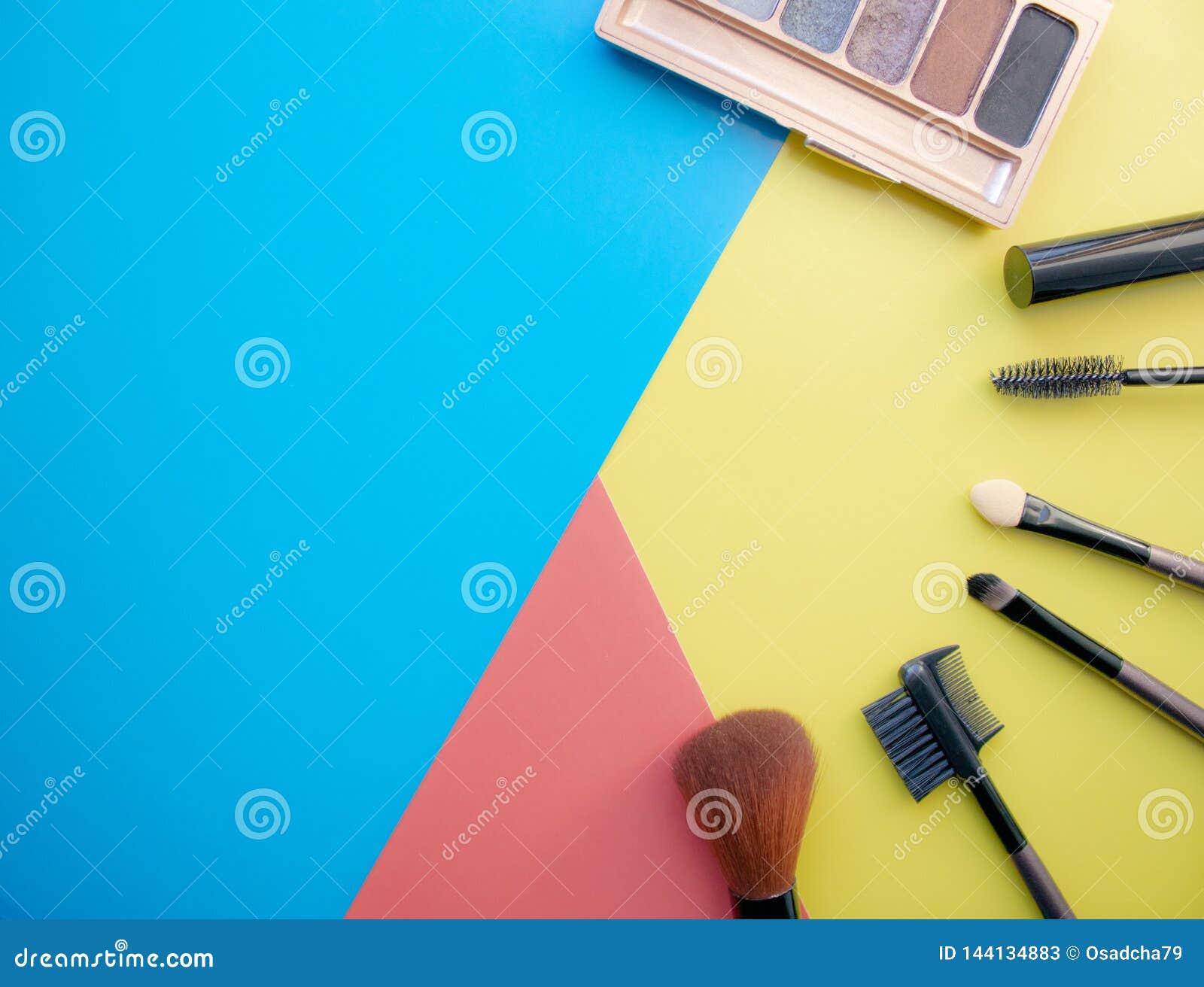 Trucco e spazzole di trucco, ombretti su un fondo colorato cosmetici per il fronte Con spazio vuoto a sinistra