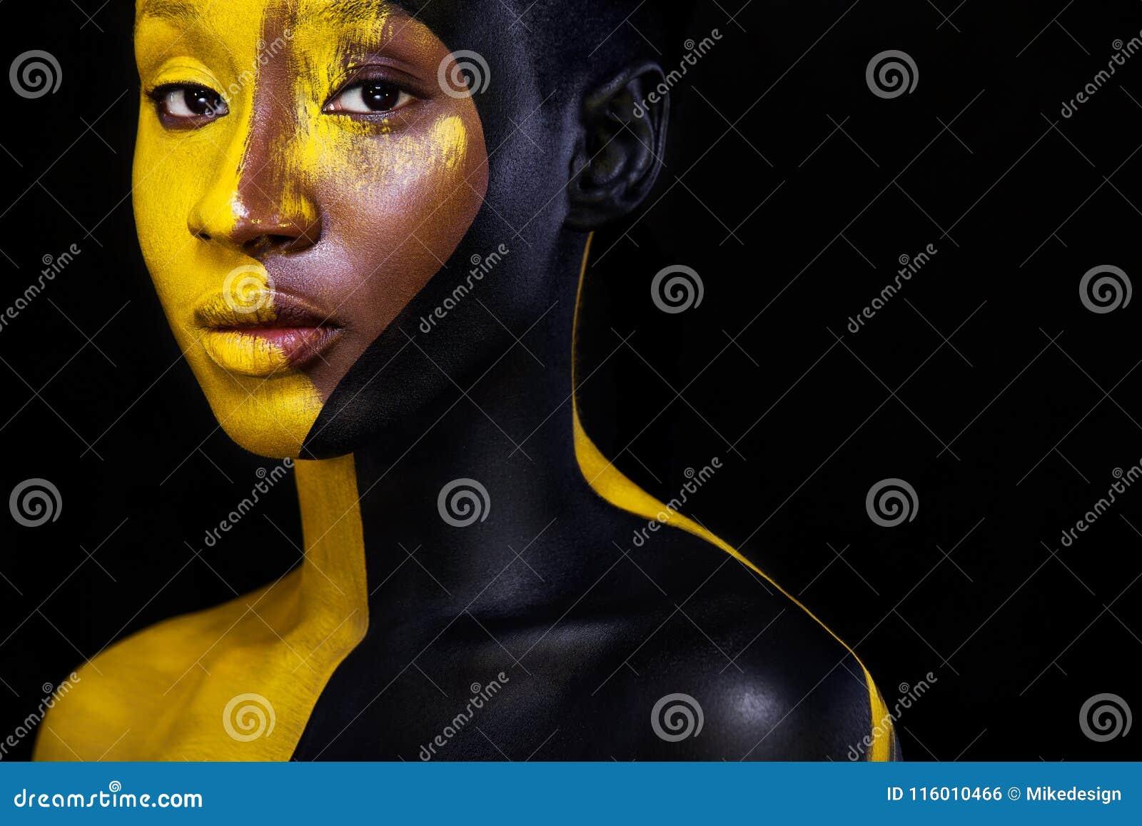 Trucco nero e giallo Giovane donna africana allegra con trucco di modo di arte