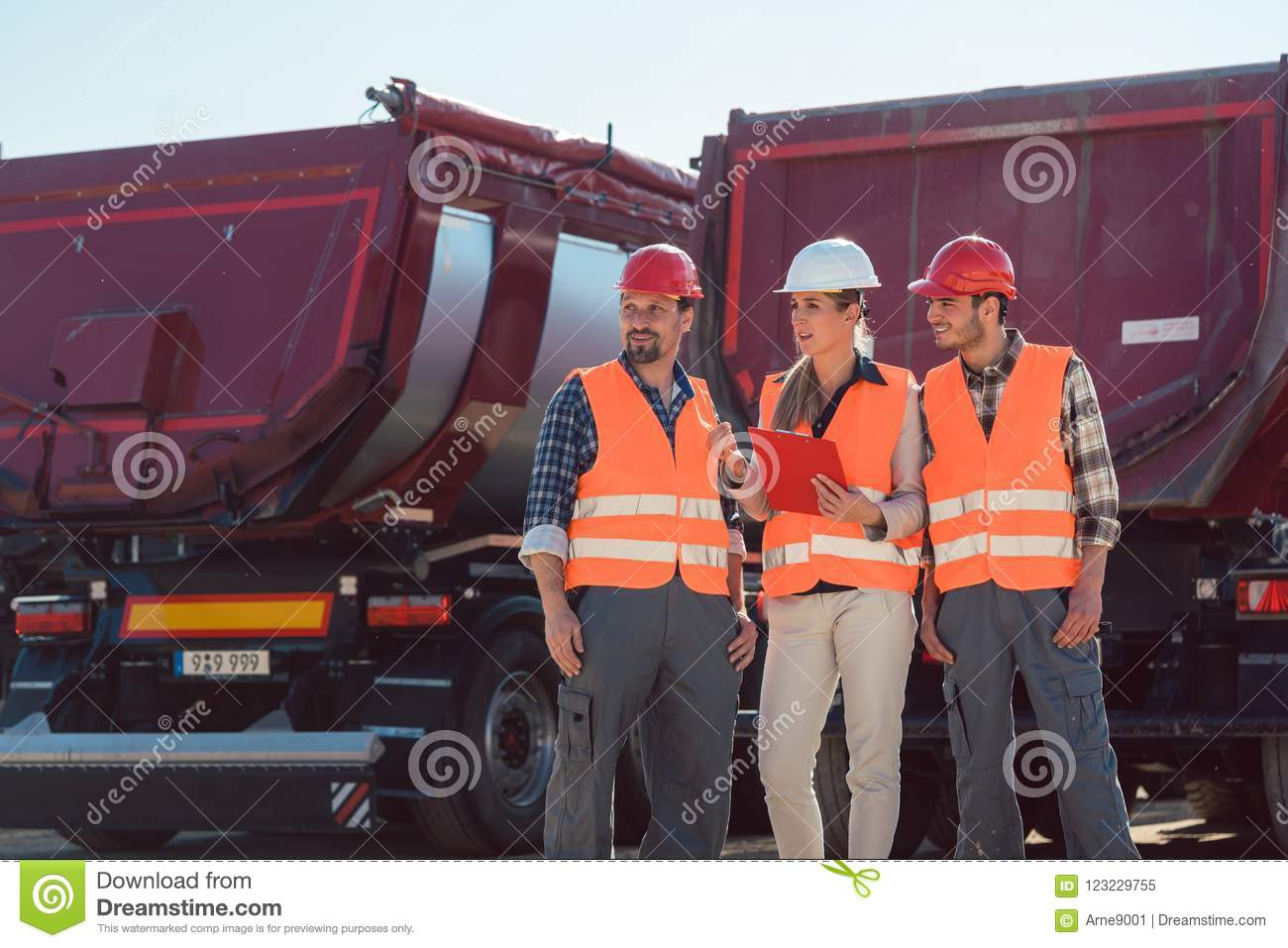 Truck drivers and dispatcher in front of lorries in freight forwarding company