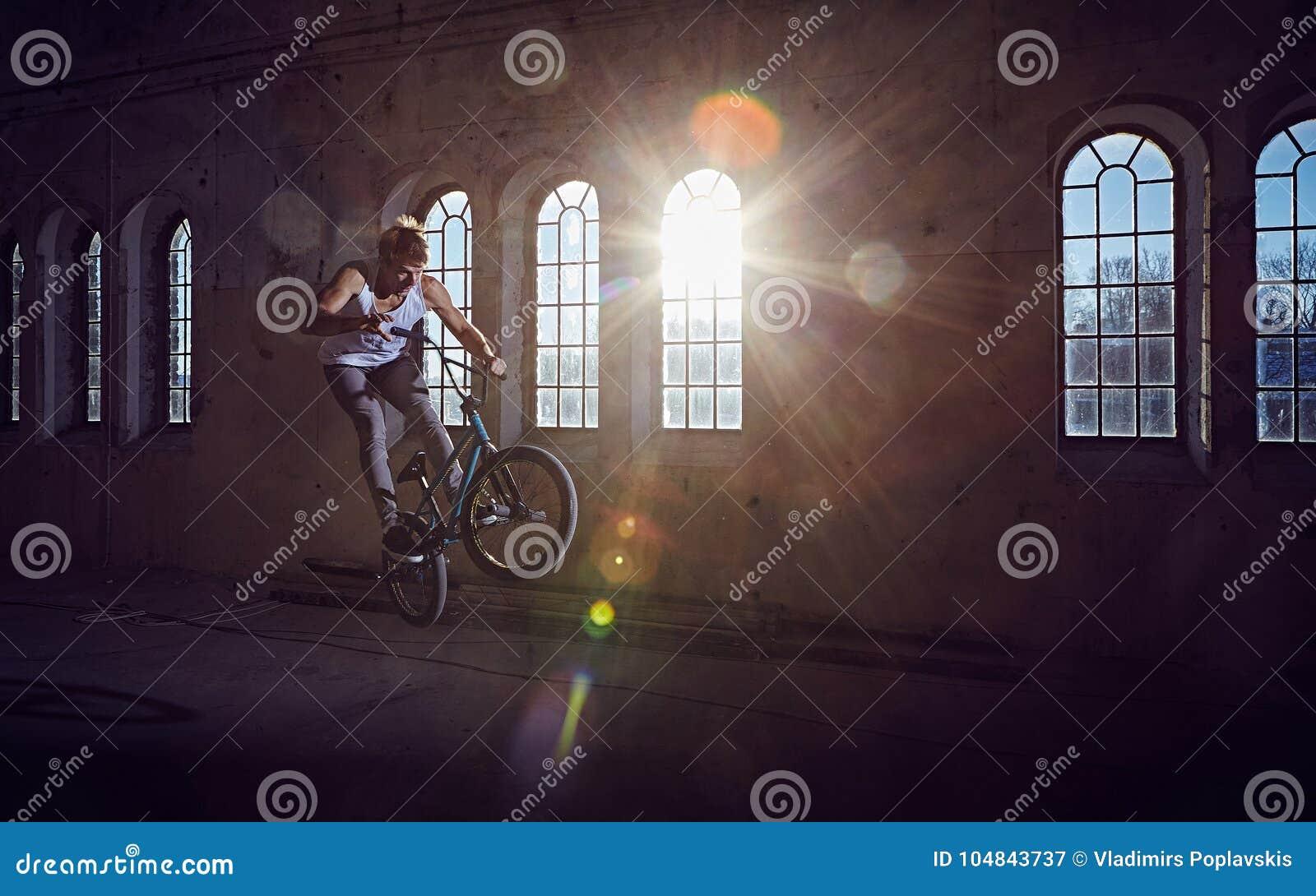 Truco de BMX y montar a caballo del salto en un pasillo con luz del sol