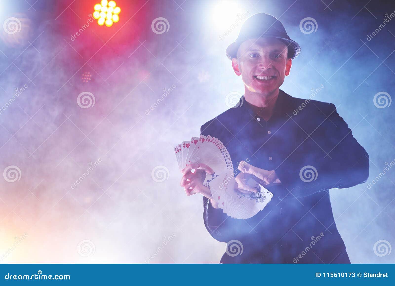 Truco de la demostración del mago con los naipes Magia o destreza, circo, jugando Prestidigitador en sitio oscuro con niebla