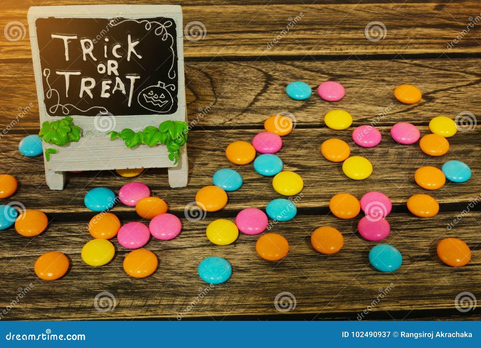 Truco o invitación de la decoración de Halloween con el caramelo en fondo de madera