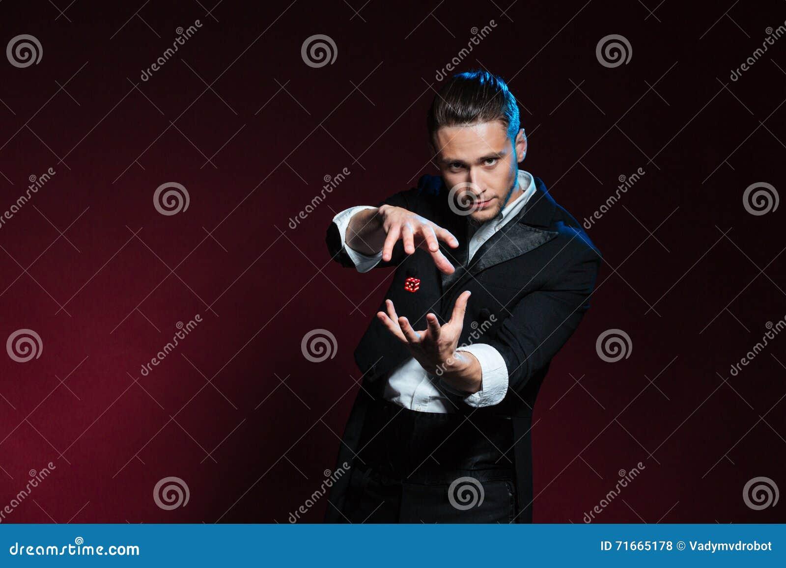 Trucos de conjuración concentrados del mago del hombre joven con los dados rojos