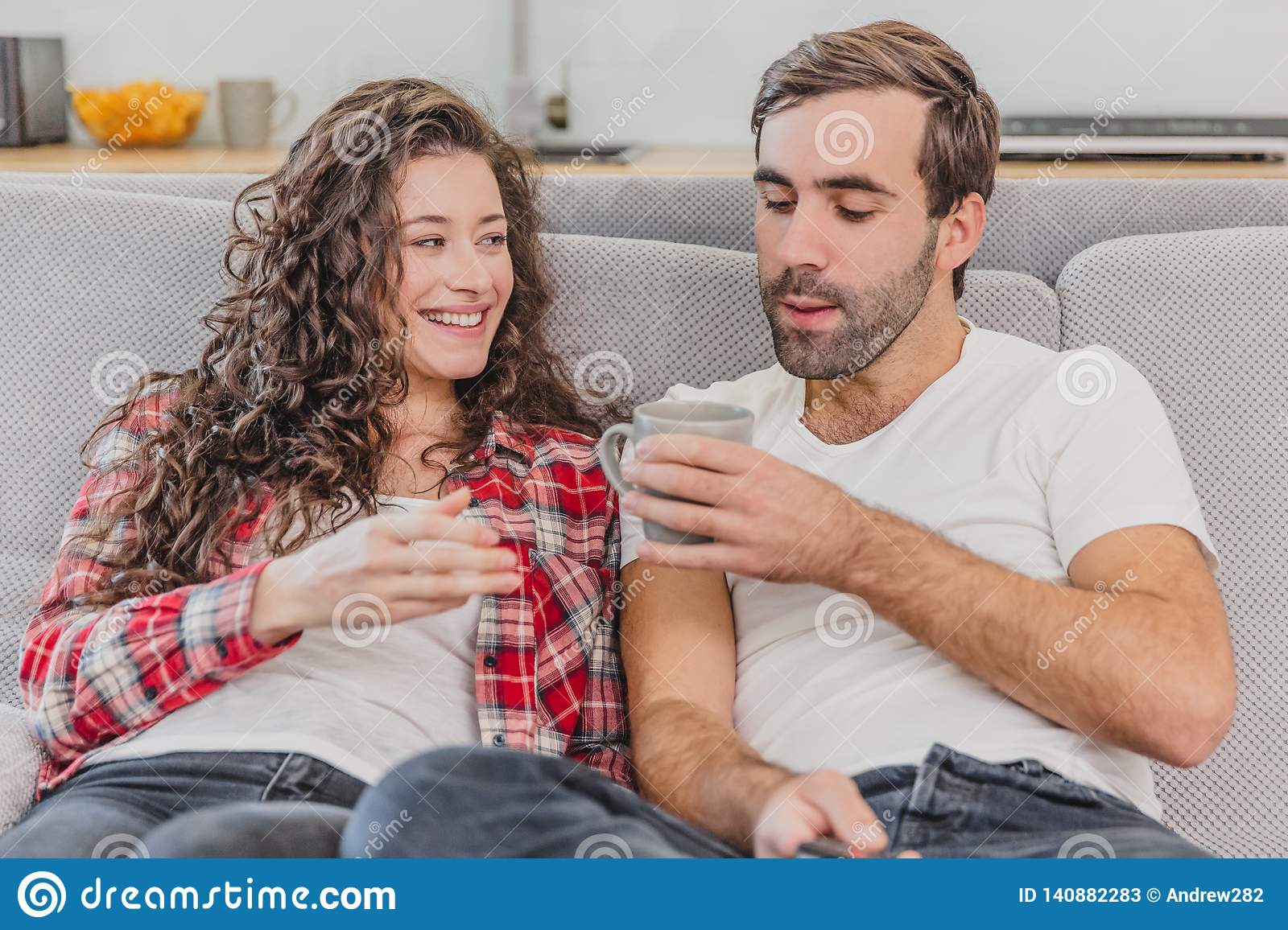 ff7a82de29c True love. Cheerful romantic couple sitting on the couch in a cozy room and  smiling