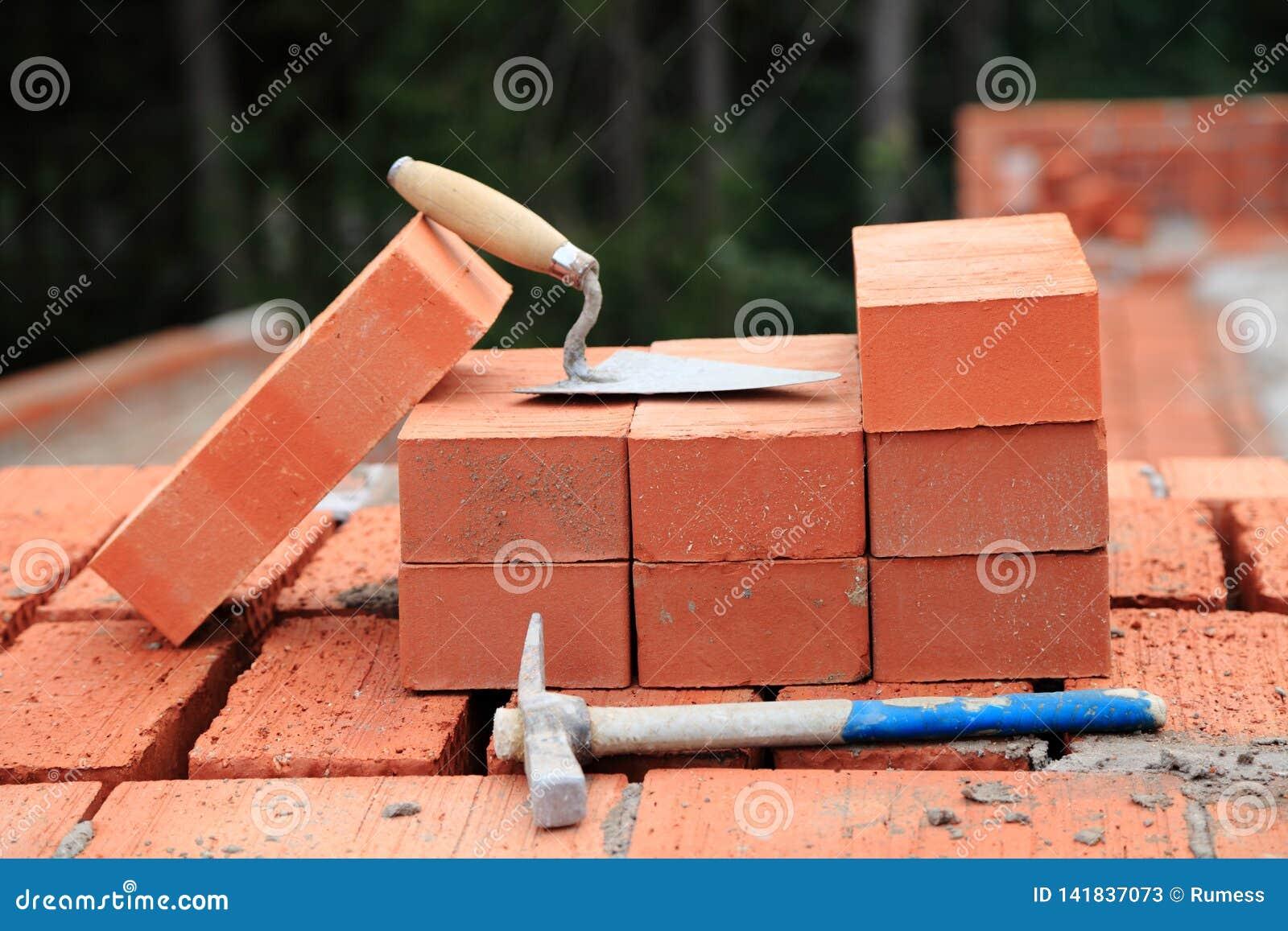 Truelle et marteau sur les briques