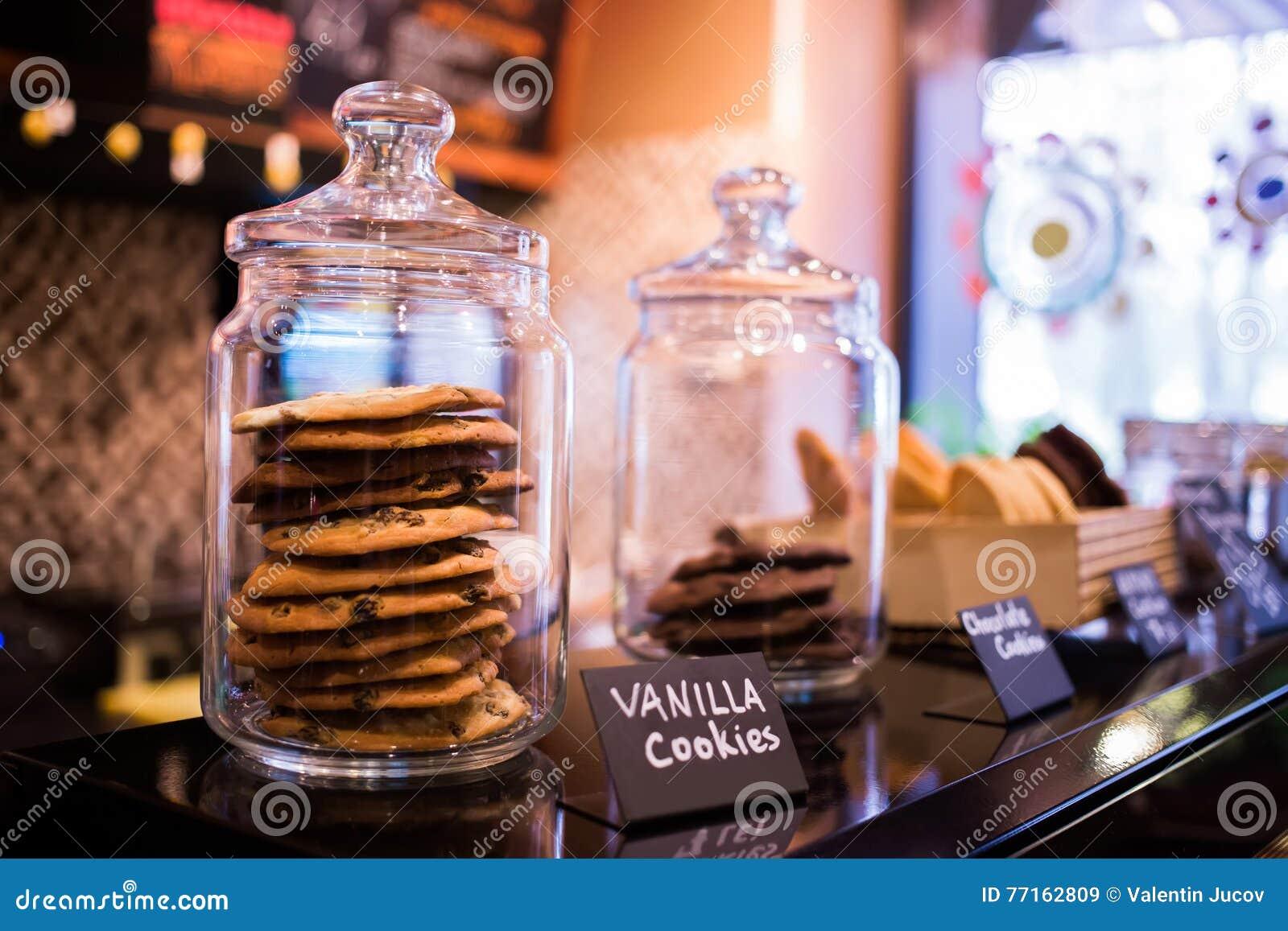 Truffe de biscuits de vanille avec du chocolat dans des pots en verre sur les étagères dans le café