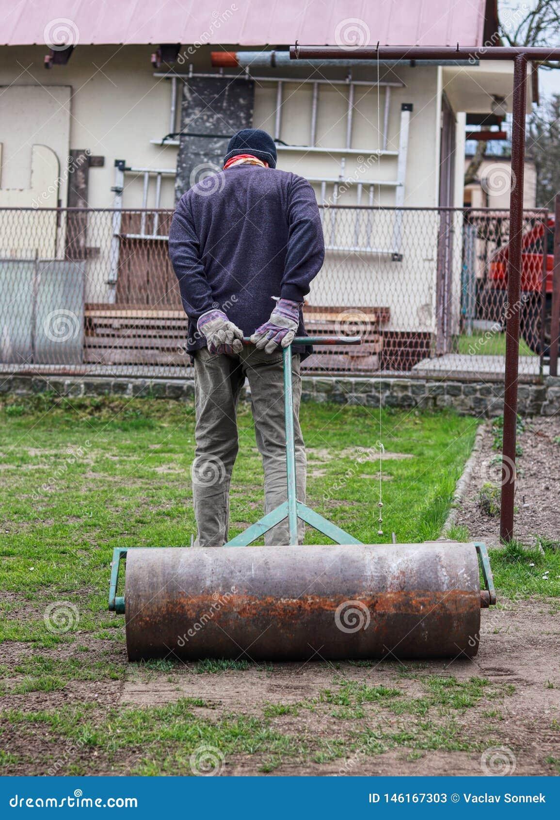 Trumma för järn för vuxen manrullning tung för bättre villkorträdgård efter vinter Människan bär den arbetande dräkten Manuellt a