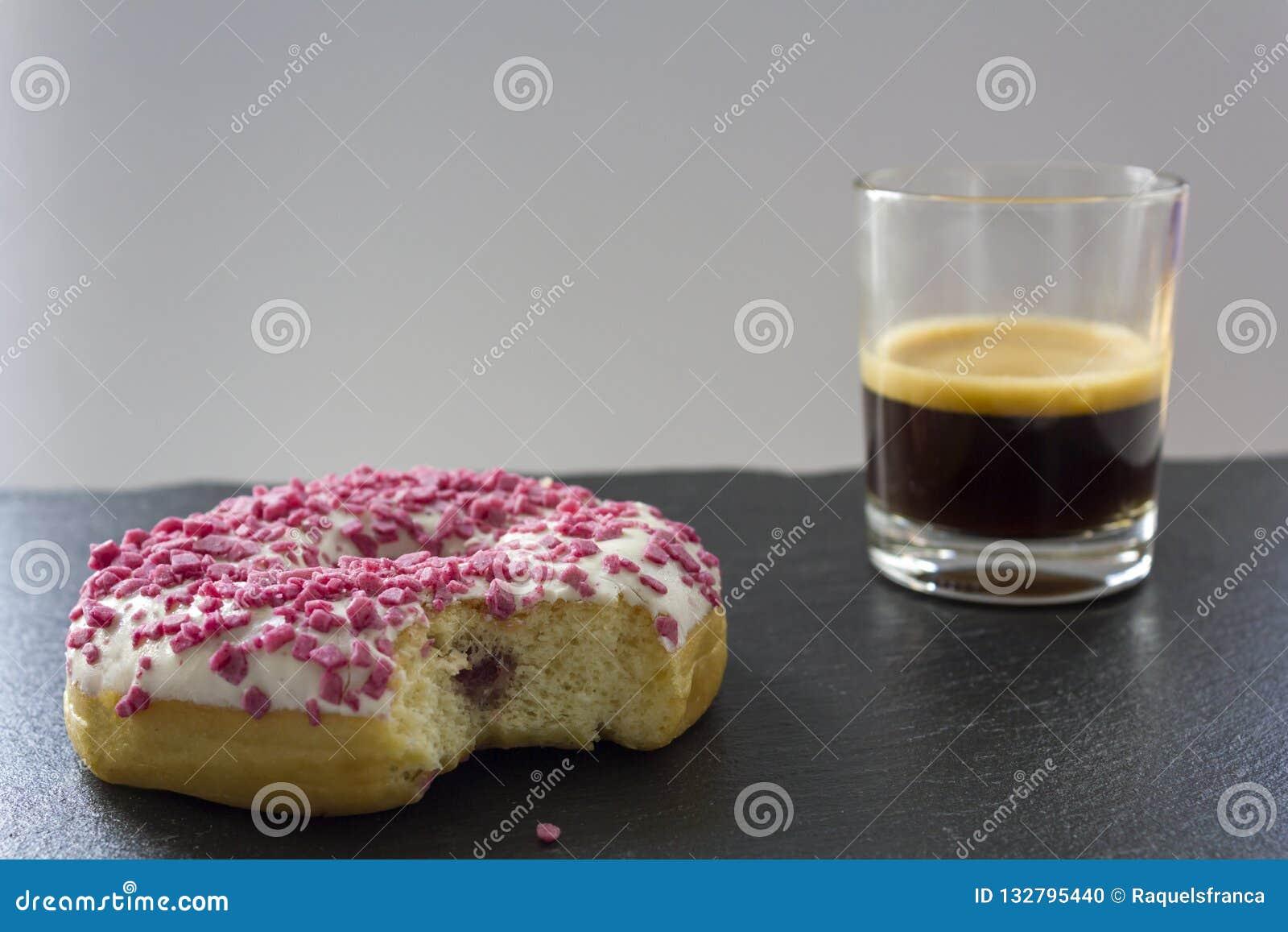 Truskawkowy pączek z kąska chybianiem i filiżanka kawy espresso kawa