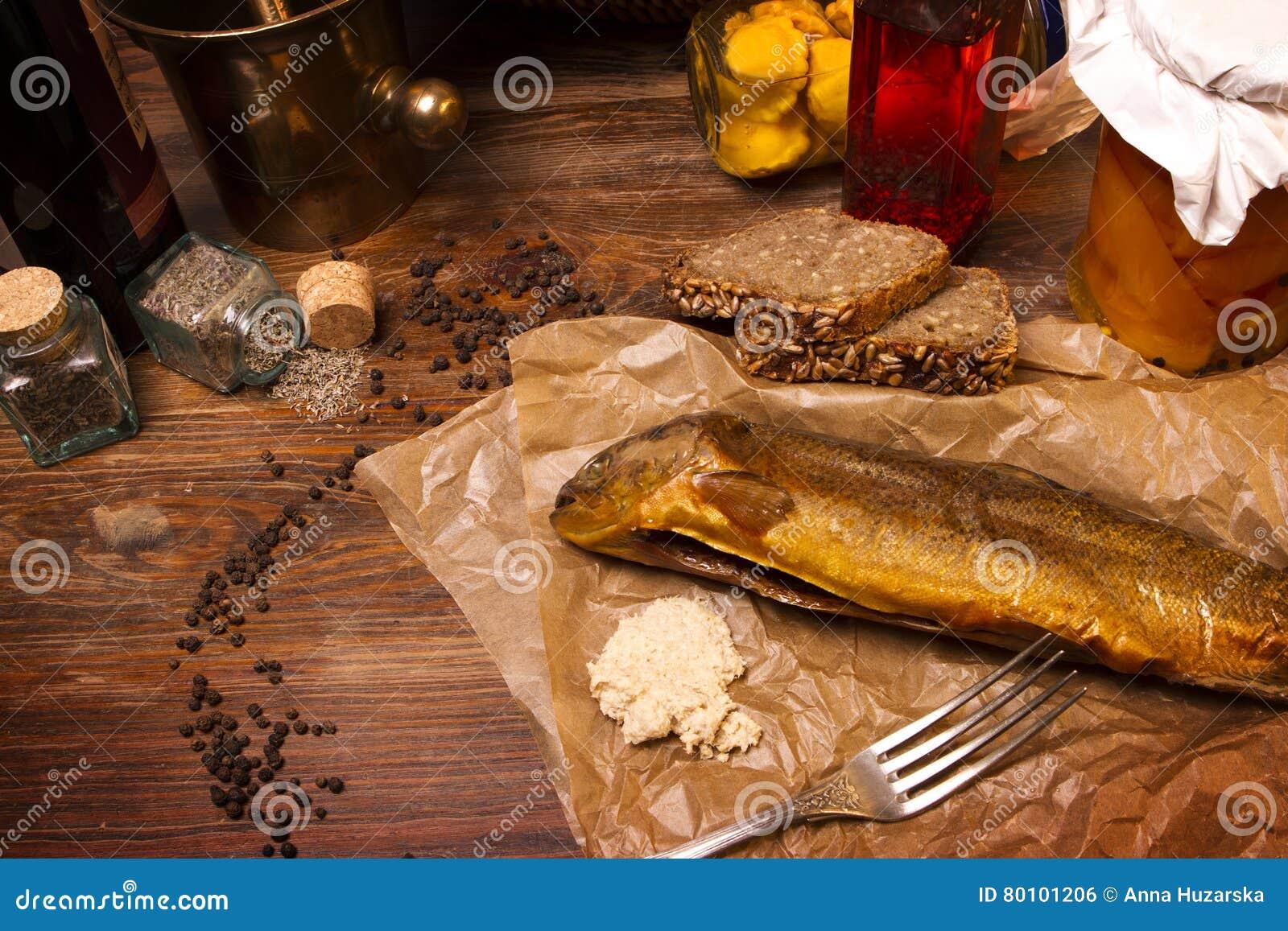 Truta fumado dos peixes com especiarias e limão em um fundo de madeira