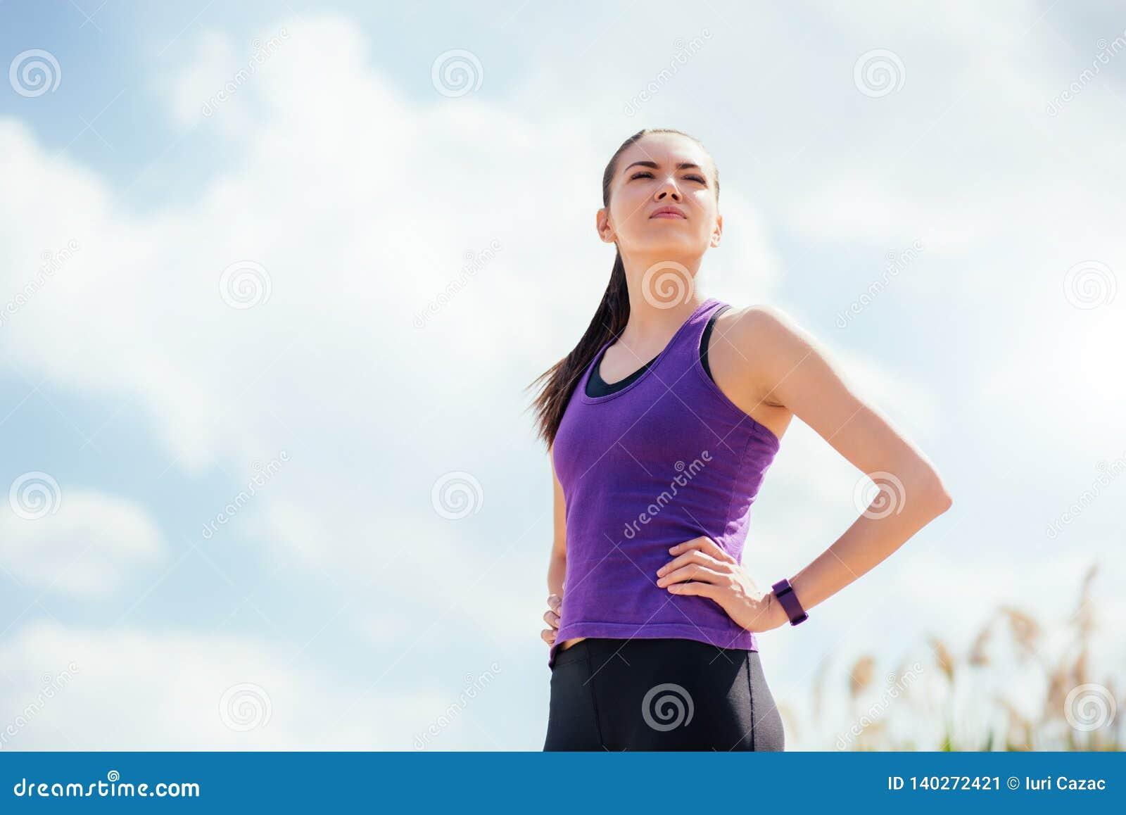 Trwanie sporty młoda piękna kobieta przed lub po treningiem i bieg Skupiający się na ćwiczeniach na nieba tle