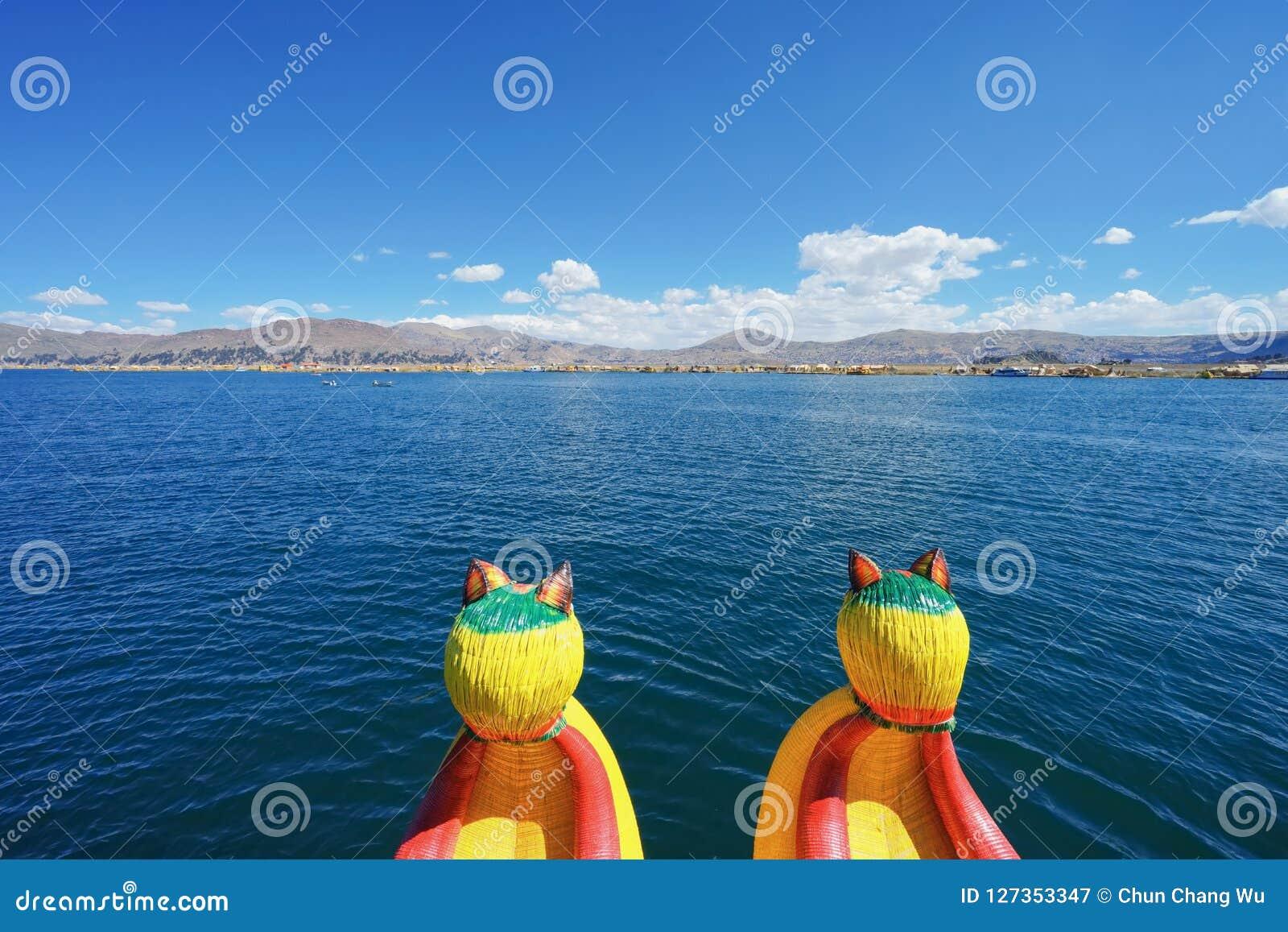 Trzcinowa łódź na Jeziornym Titicaca z pięknym niebieskim niebem I trzcinowa wyspa jest w przodzie, dalekim
