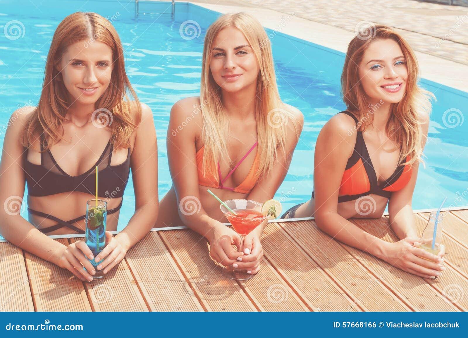 Trzy ładnej dziewczyny z koktajlami przy basenem