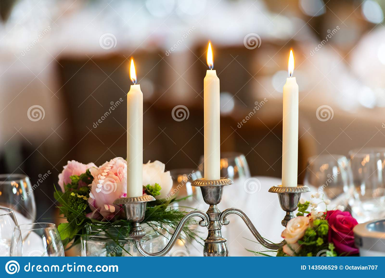 Trzy świeczki w świeczka właścicielu na dekorującym stole