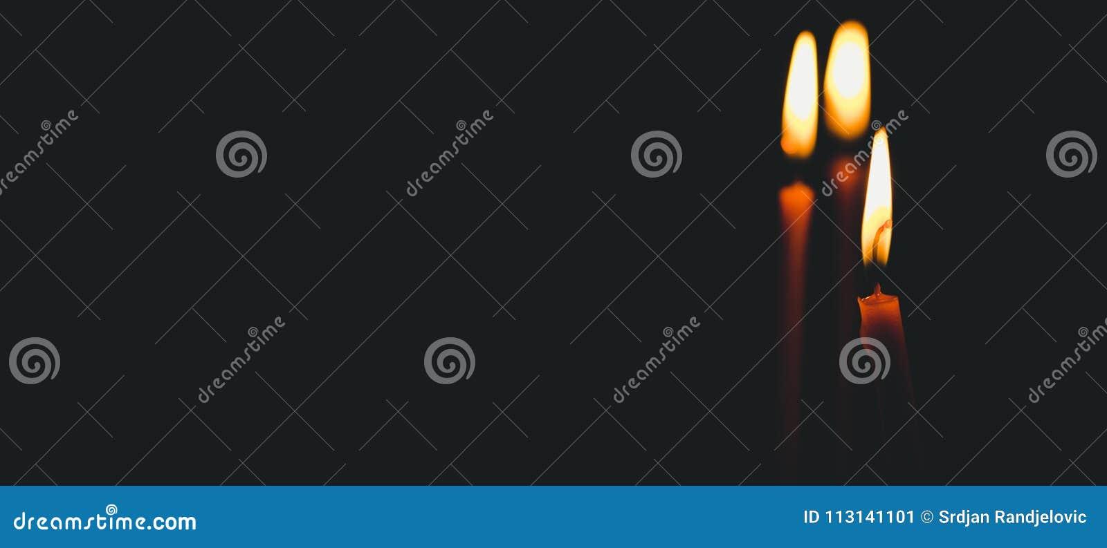 Trzy żółtej wosk świeczki pali z światłem płomień iluminują przestrzeń w kościół, religii pojęcie