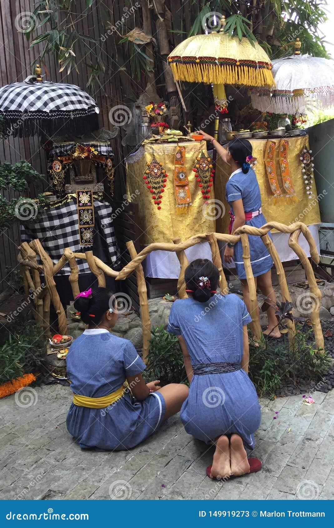 Trzy balijczyka kobieta przed małą świątynią dla modlitwy