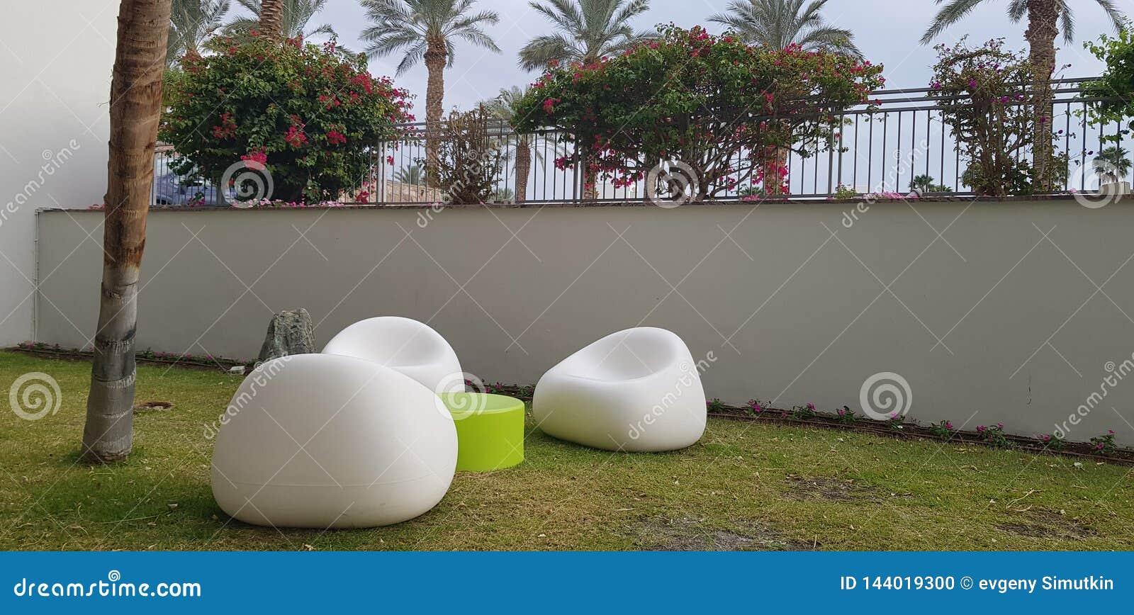 Trzy biel krzese? plastikowego pobytu pusty round ma?y st?? na trawie