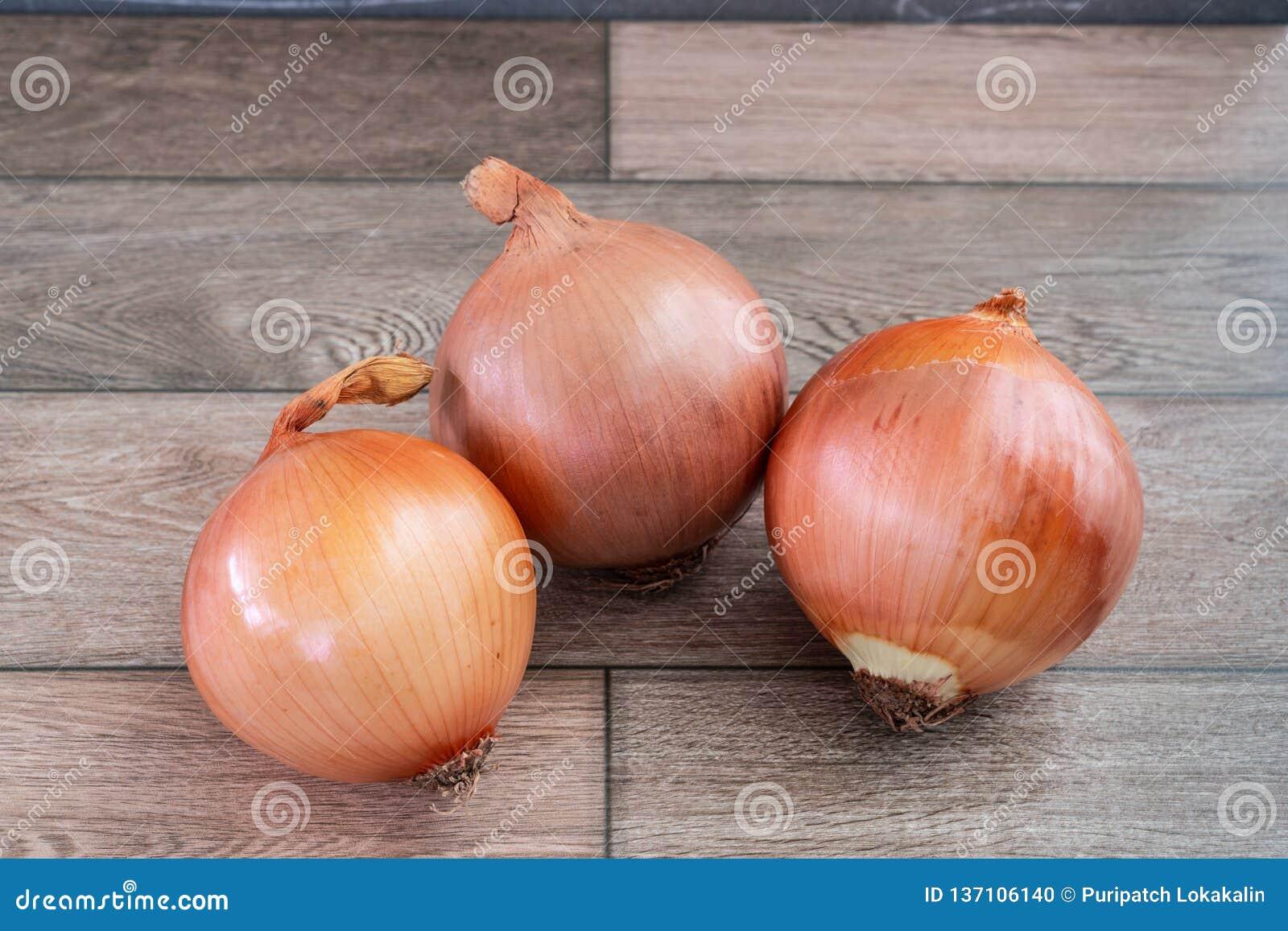Trzy cebuli na drewnianej podłodze