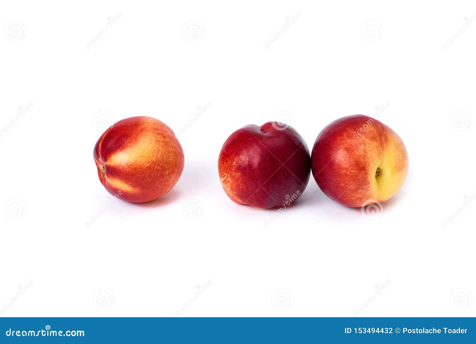 Trzy czerwonej łysej brzoskwini na białym tle Brzoskwini zbliżenia czerwony kolor