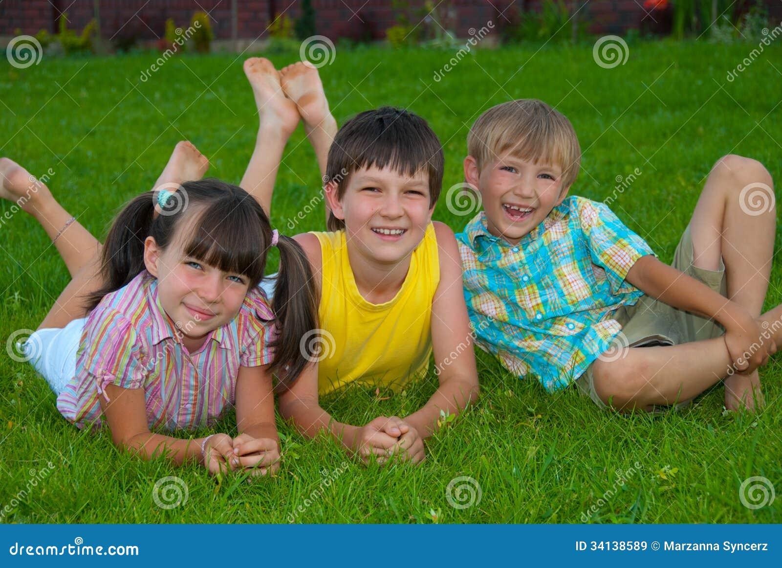 Trzy dzieciaka na trawie
