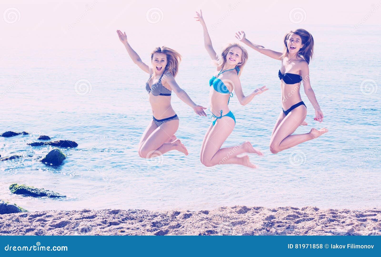 Trzy dziewczyny skacze na plaży