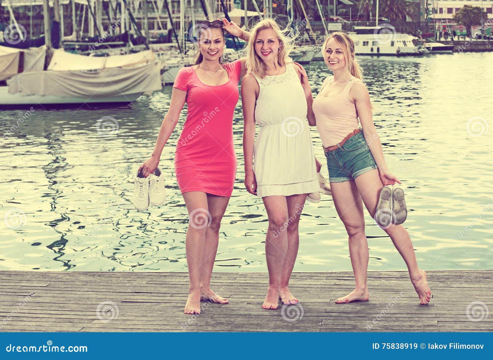 Trzy dziewczyny stoi na nabrzeżu