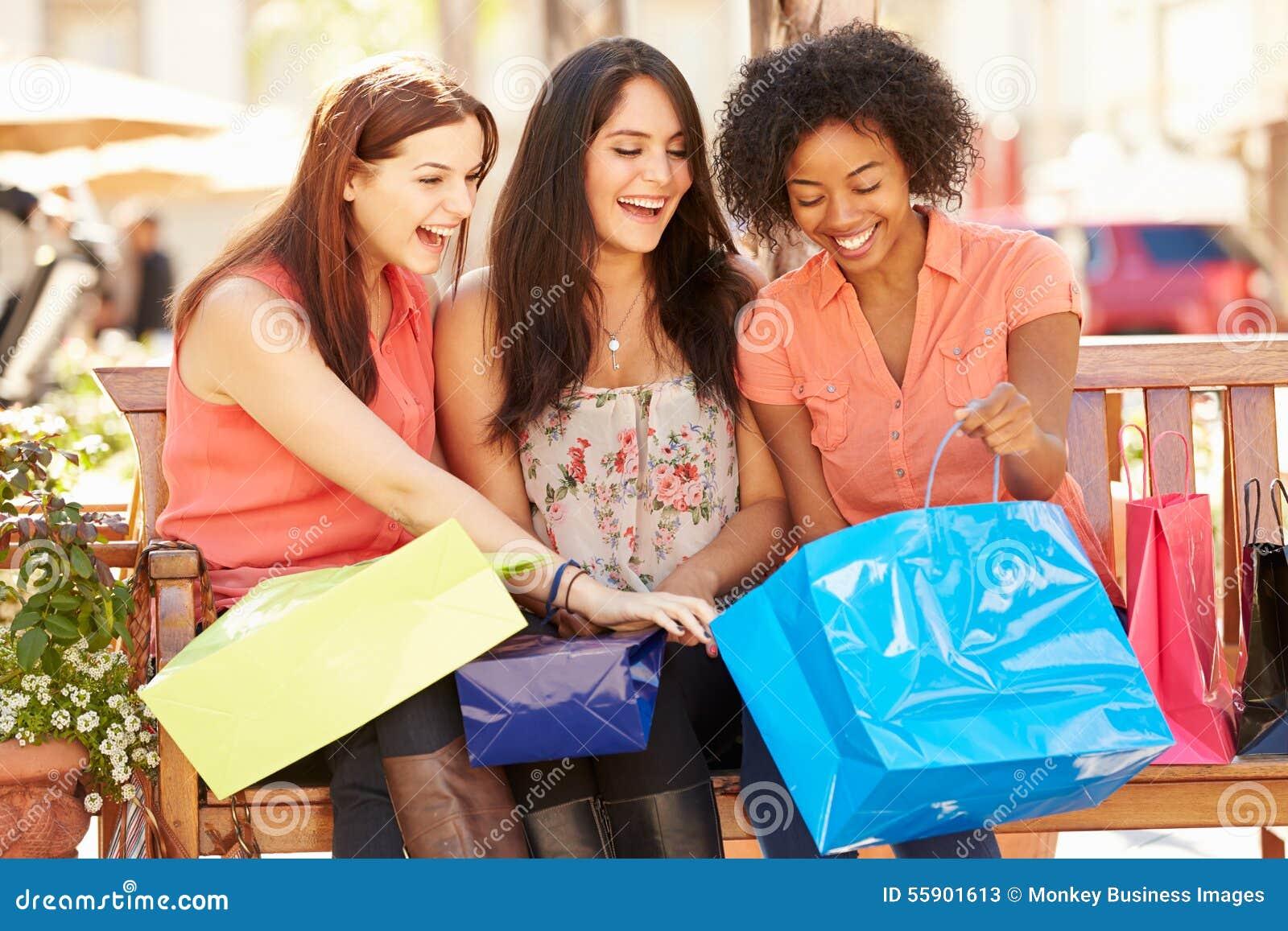 Trzy Żeńskiego przyjaciela Siedzi W centrum handlowym Z torba na zakupy