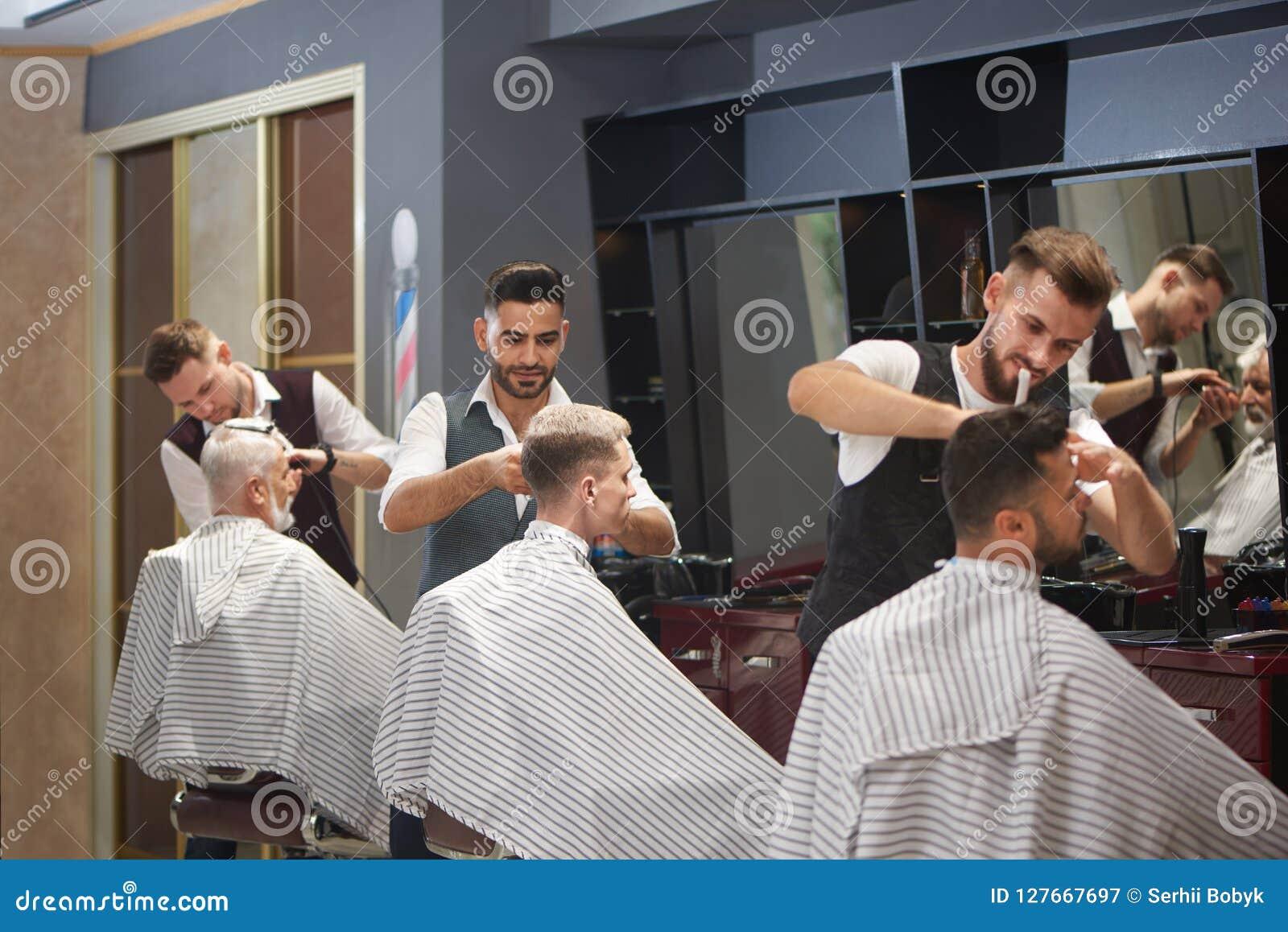 Trzy fachowego fryzjera męskiego żyłuje, ciie i projektuje, męskiego klienta ` włosy