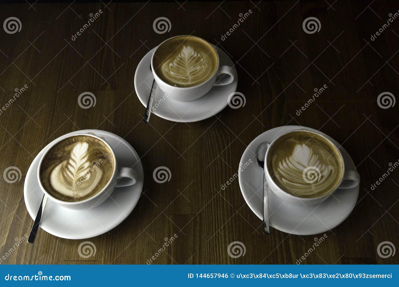 Trzy filiżanki gotowej słuzyć kawę z mlekiem