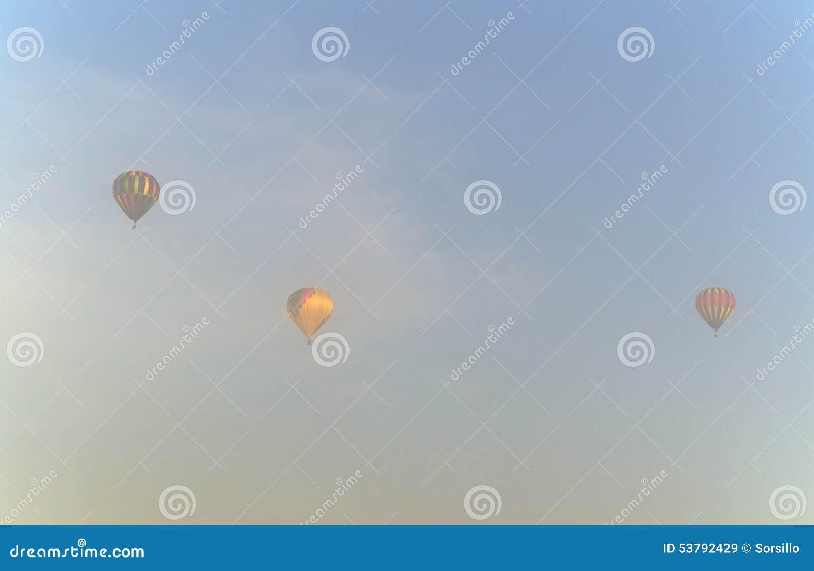 Trzy gorące powietrze balonu w ranek mgle