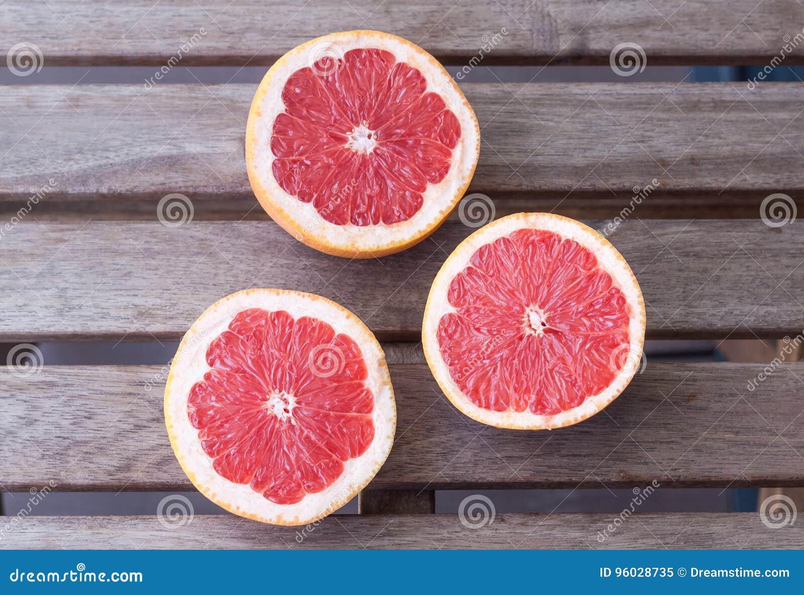 Trzy grapefruitowej połówki na drewnianym tle