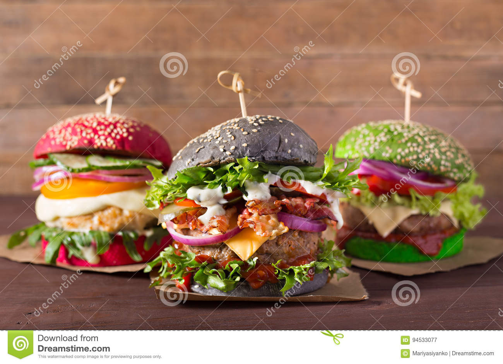 Trzy hamburgeru z różnymi chlebowymi babeczkami na drewnianym tle