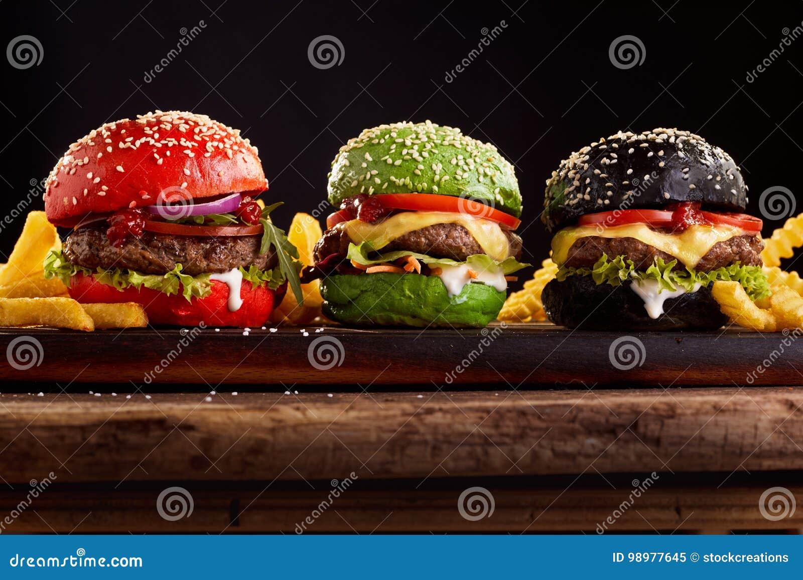 Trzy, hamburgery na kolorowych spłodzonych babeczkach