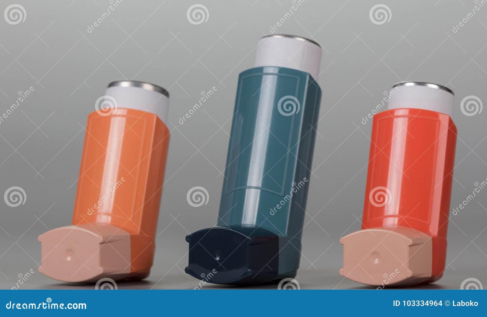 Trzy inhalatorów aerosol na popielatym tle