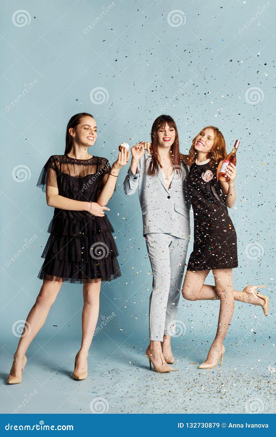 Trzy kobiety śmia się świętują wakacyjnego mieć zabawę i jeść zasycha pod latającymi confetti Dziewczyny pozuje i ono uśmiecha si